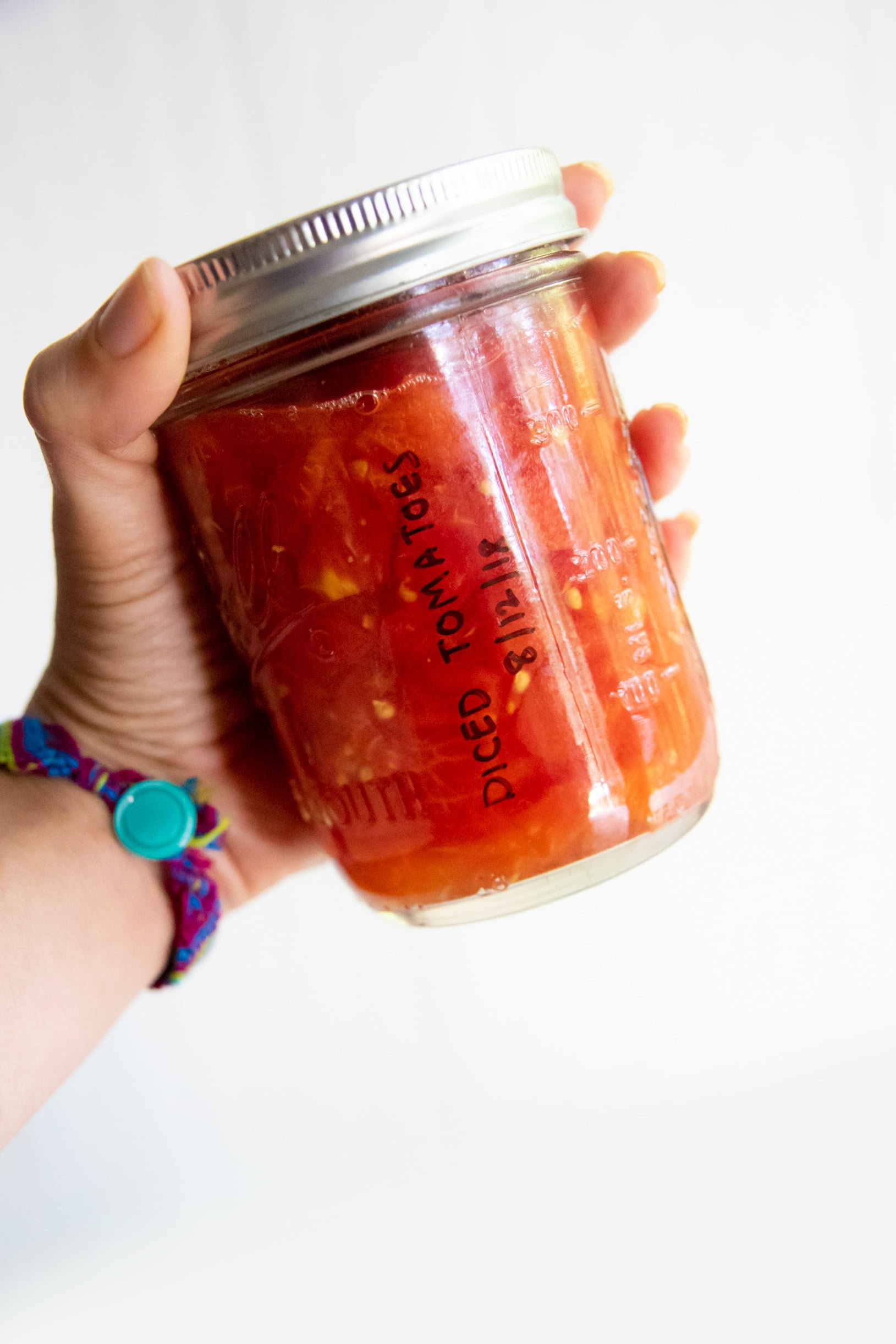 Hand holding a glass jar of diced tomatoes - how to can diced tomatoes
