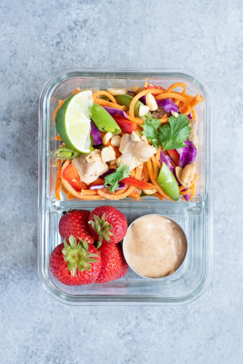 Overhead shot of Meal Prep Chicken Pad Thai with Sweet Potato Noodles packed into a glass lunch container with strawberries