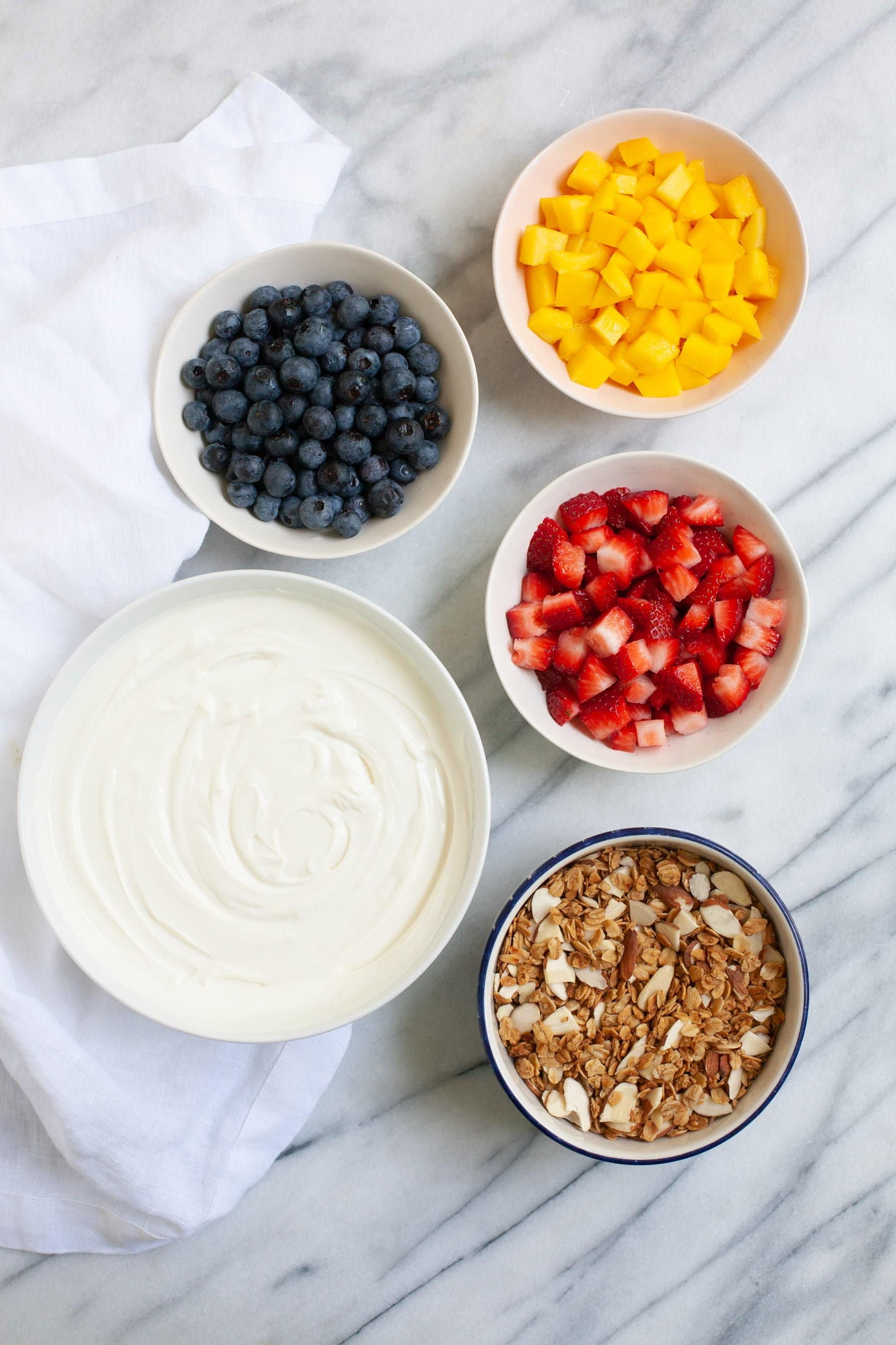 Overhead shot of ingredients for Meal Prep Fruit and Yogurt Parfaits - yogurt, fruit, and granola in bowls