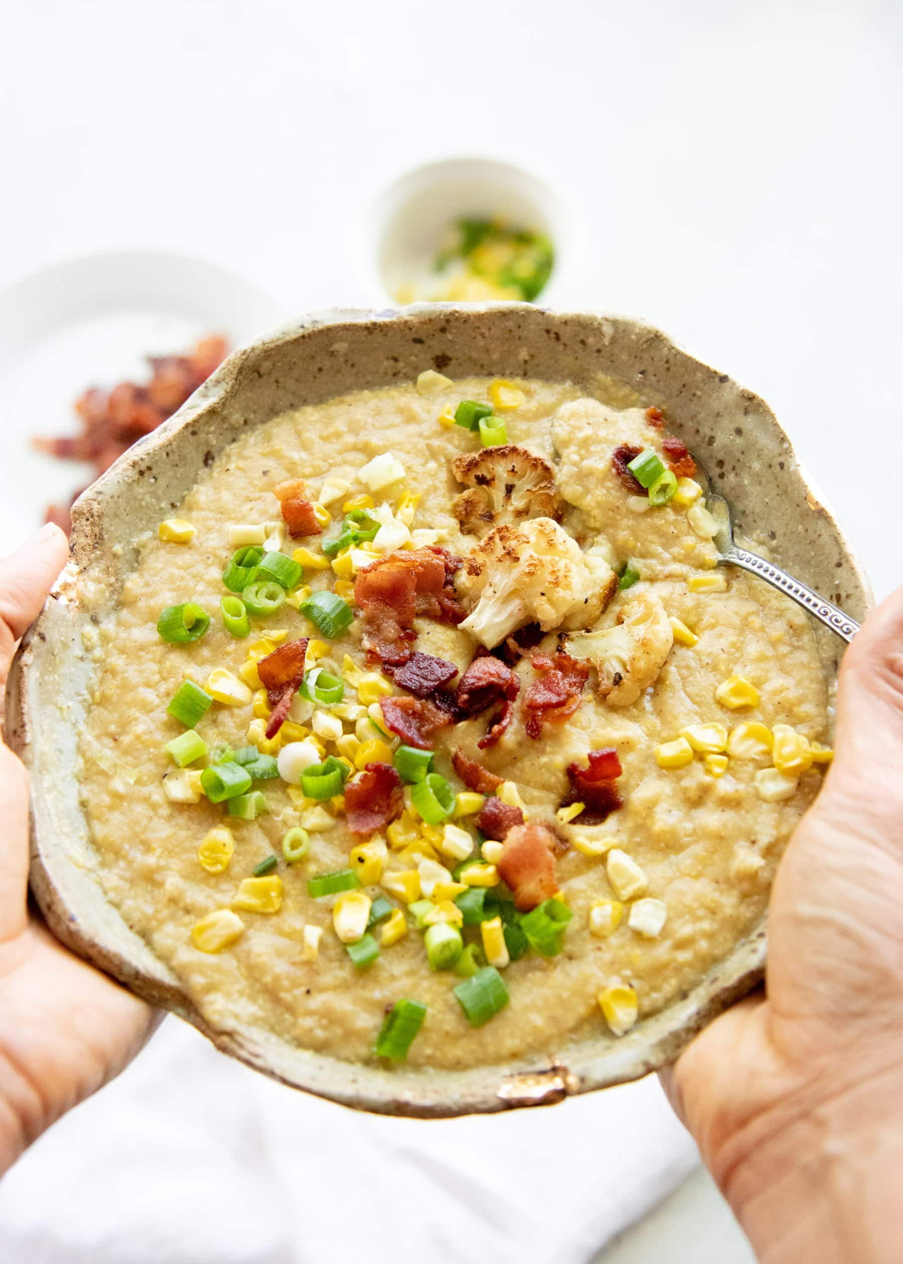 Hands holding a bowl full of Roasted Corn and Cauliflower Chowder, topped with corn, green onions, and bacon