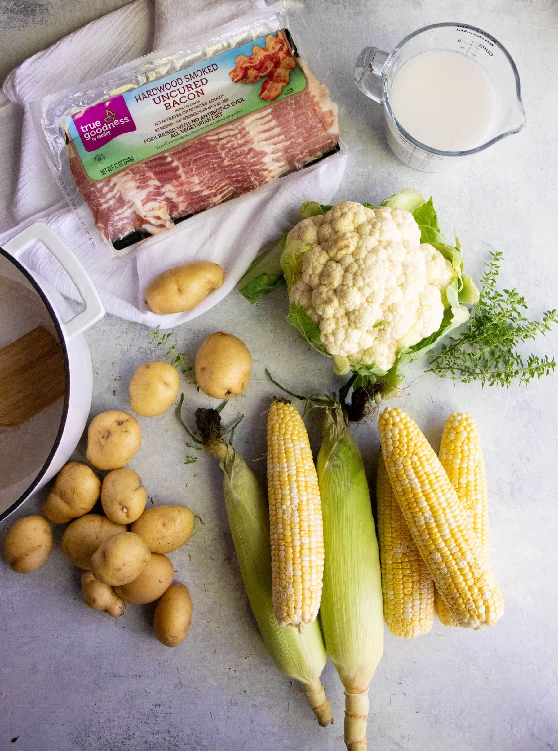 Overhead shot of soup ingredients-- corn, potatoes, cauliflower, bacon, coconut milk