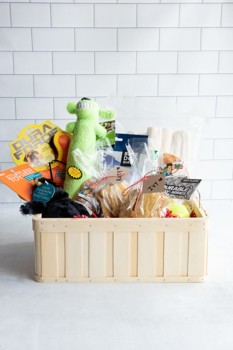 Tan basket filled with dog treats and toys