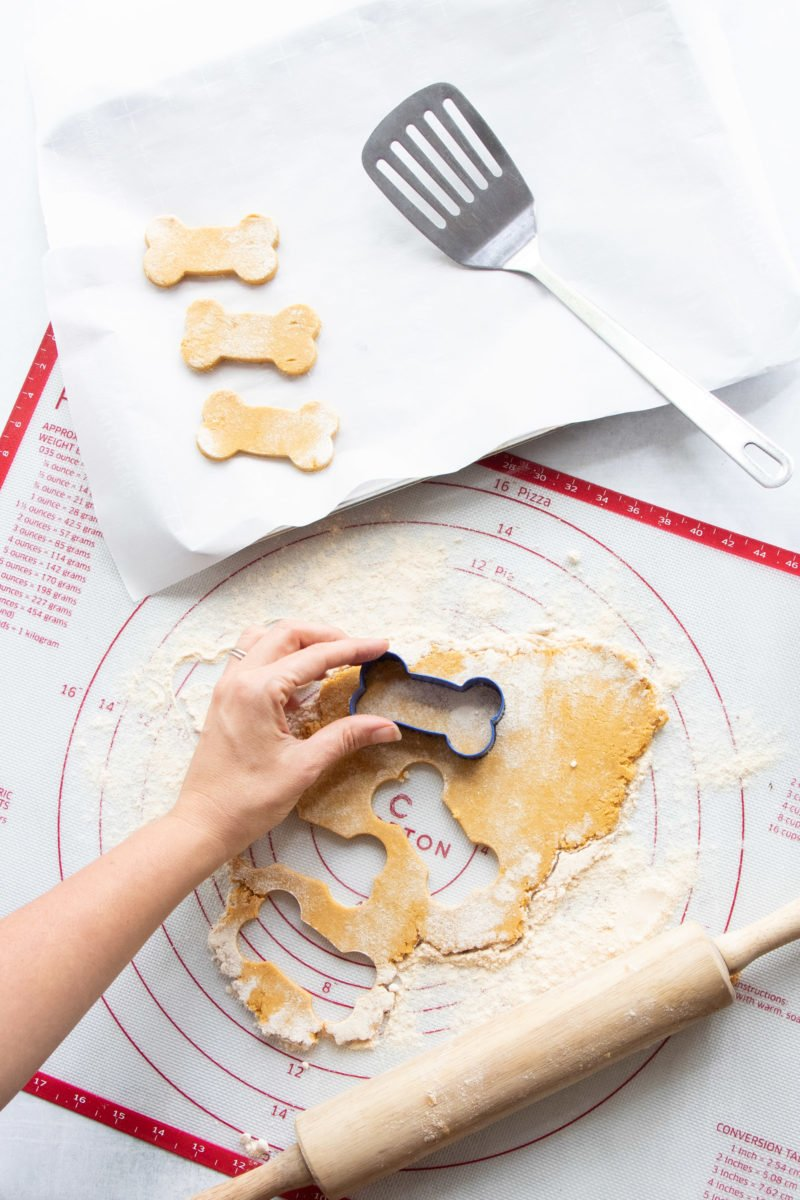 Hand using a bone-shaped cookie cutter to cut dough for Grain-Free Pumpkin Coconut Dog Treats