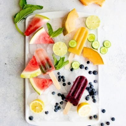 Overhead shot of three flavors of frozen fruit pops arranged on a tray of crushed ice, surrounded by fruit