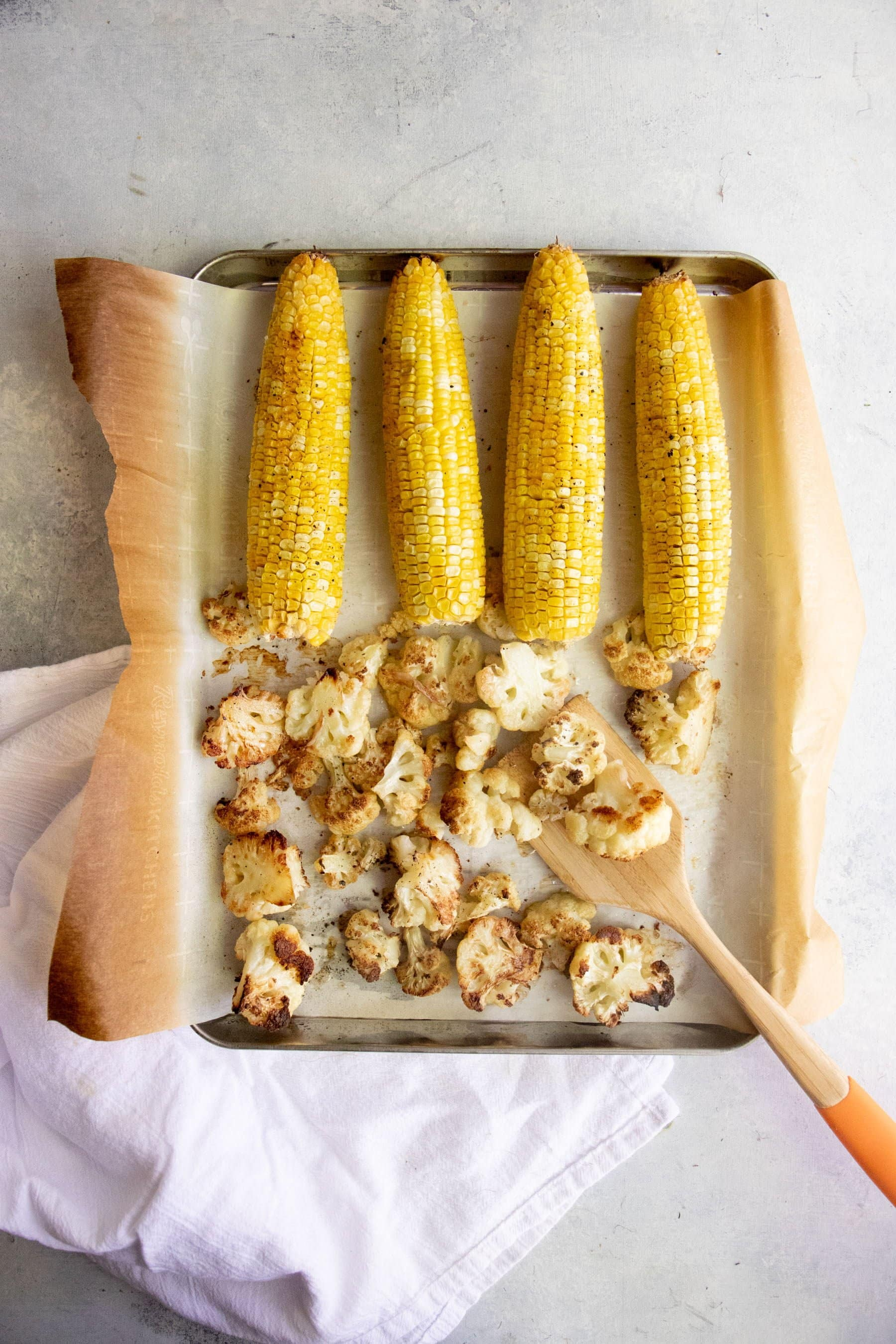 Ears of corn and cut cauliflower arranged on a baking sheet lined with parchment