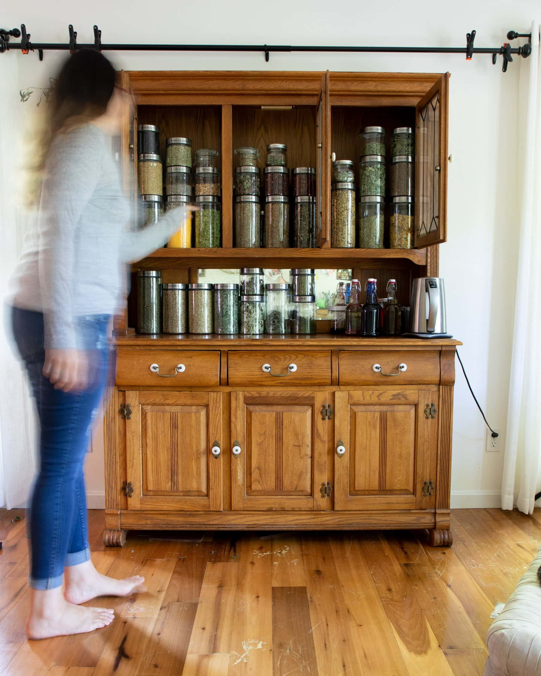 Blurred woman walking up to a wooden apothecary cabinet full of medicinal herbs in glass jars