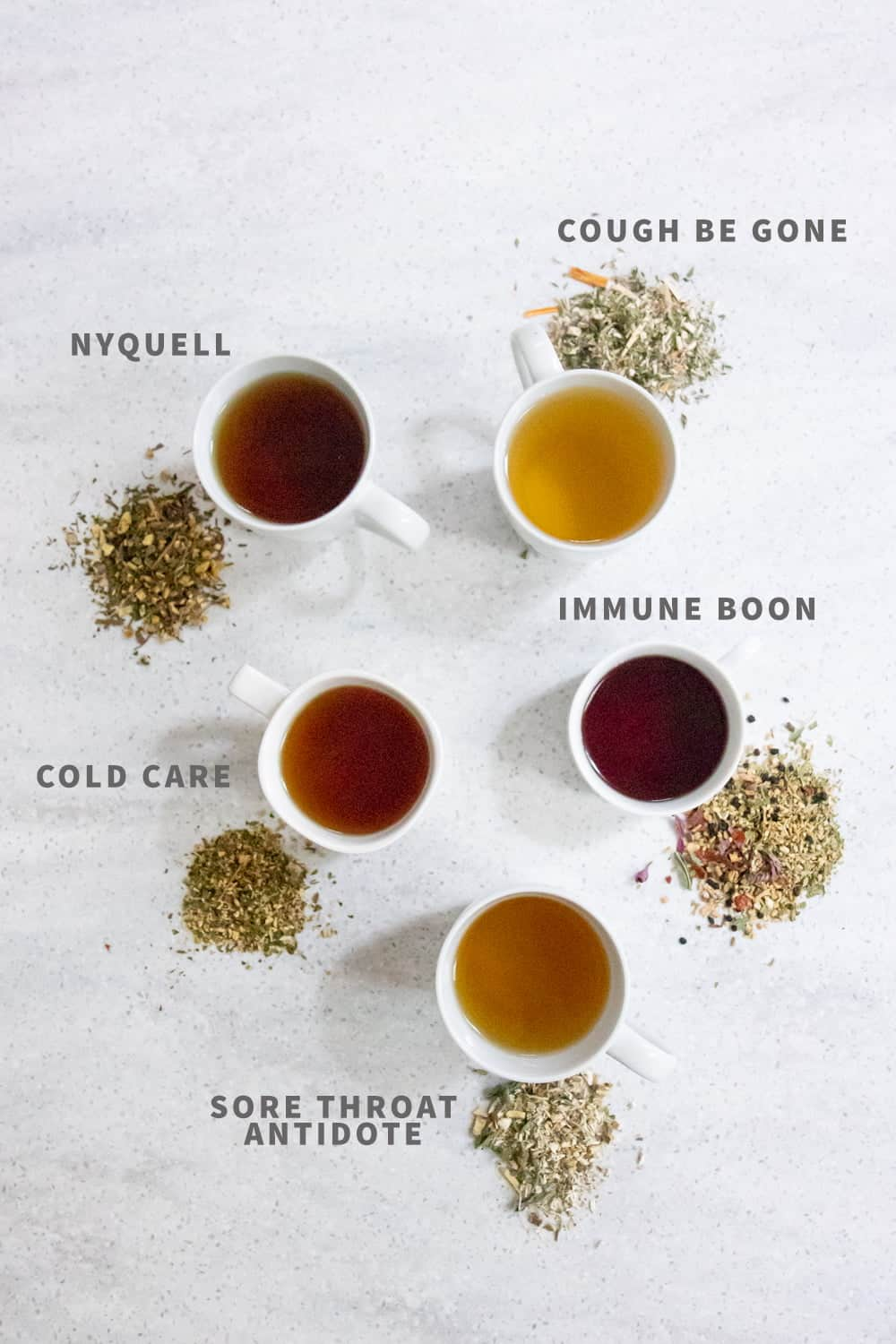 Five cups of herbal tea in white teacups, with the herbs for each nearby. From top clockwise: Cough Be Gone, Immune Boon, Sore Throat Antidote, Cold Care, and Nyquell teas