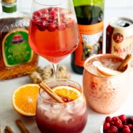 Three different cocktails surrounded by the ingredients to make them - cinnamon sticks, hard cider, whiskey, wine, cranberries, orange, ginger