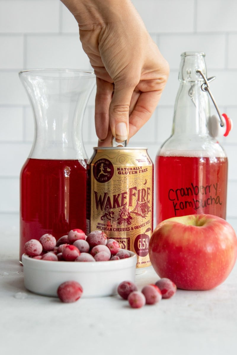 Hand opening a can of hard cider, next to carafes of kombucha and cranberry juice, with frozen cranberries and a whole apple nearby