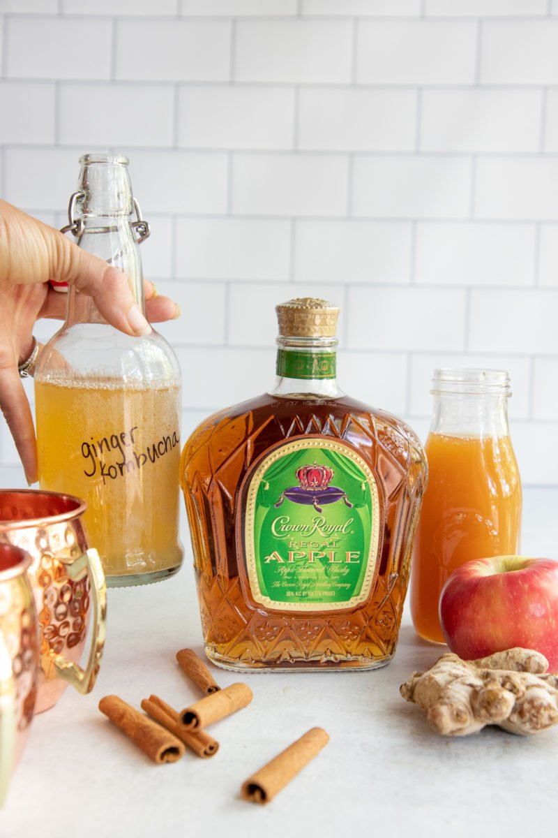 Bottle of Crown Royal Apple next to some ginger kombucha, cinnamon sticks, ginger, and a whole apple, with copper mugs in the corner