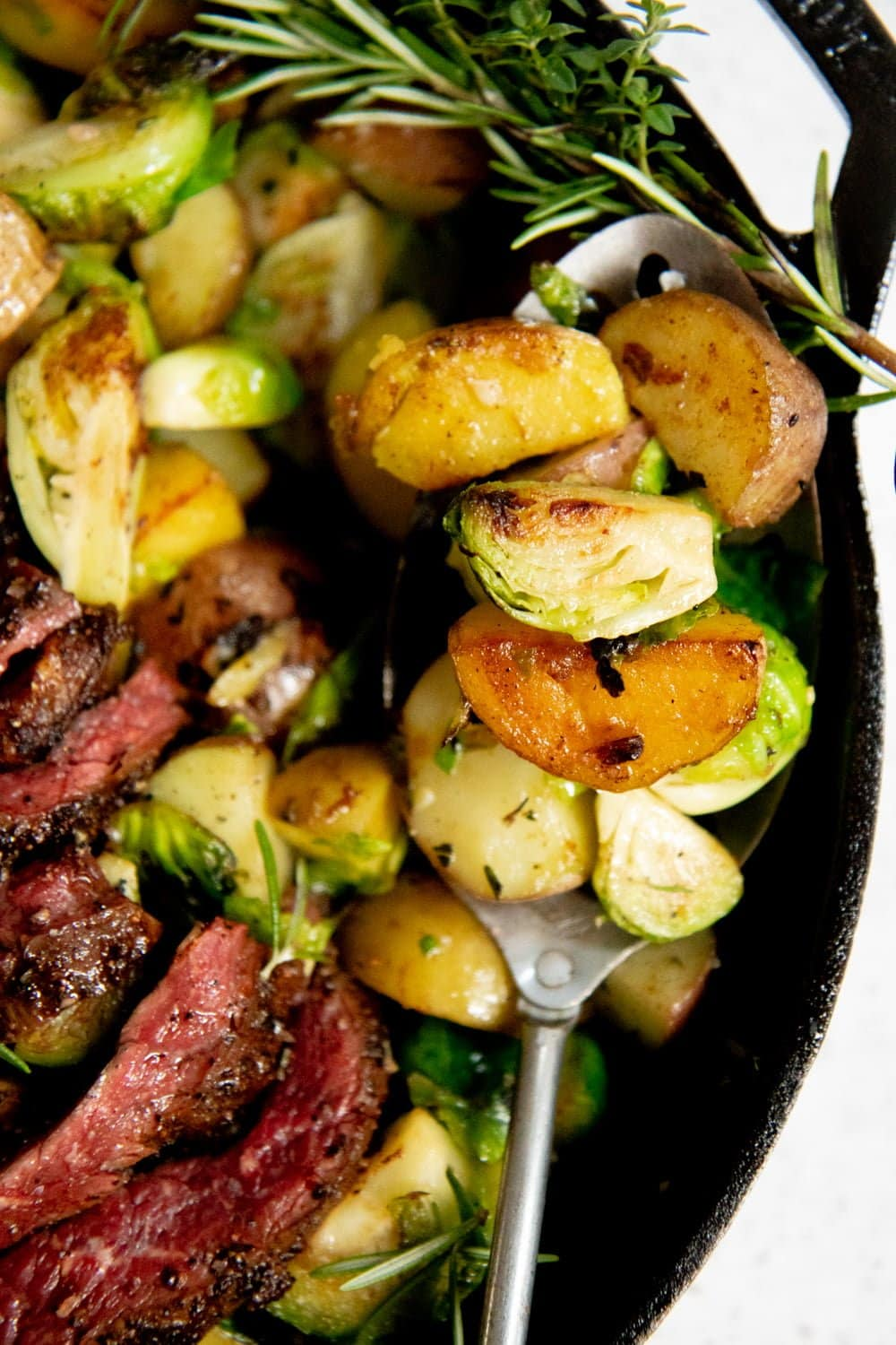 Close-up of cooked potatoes and Brussels sprouts in a cast iron skillet