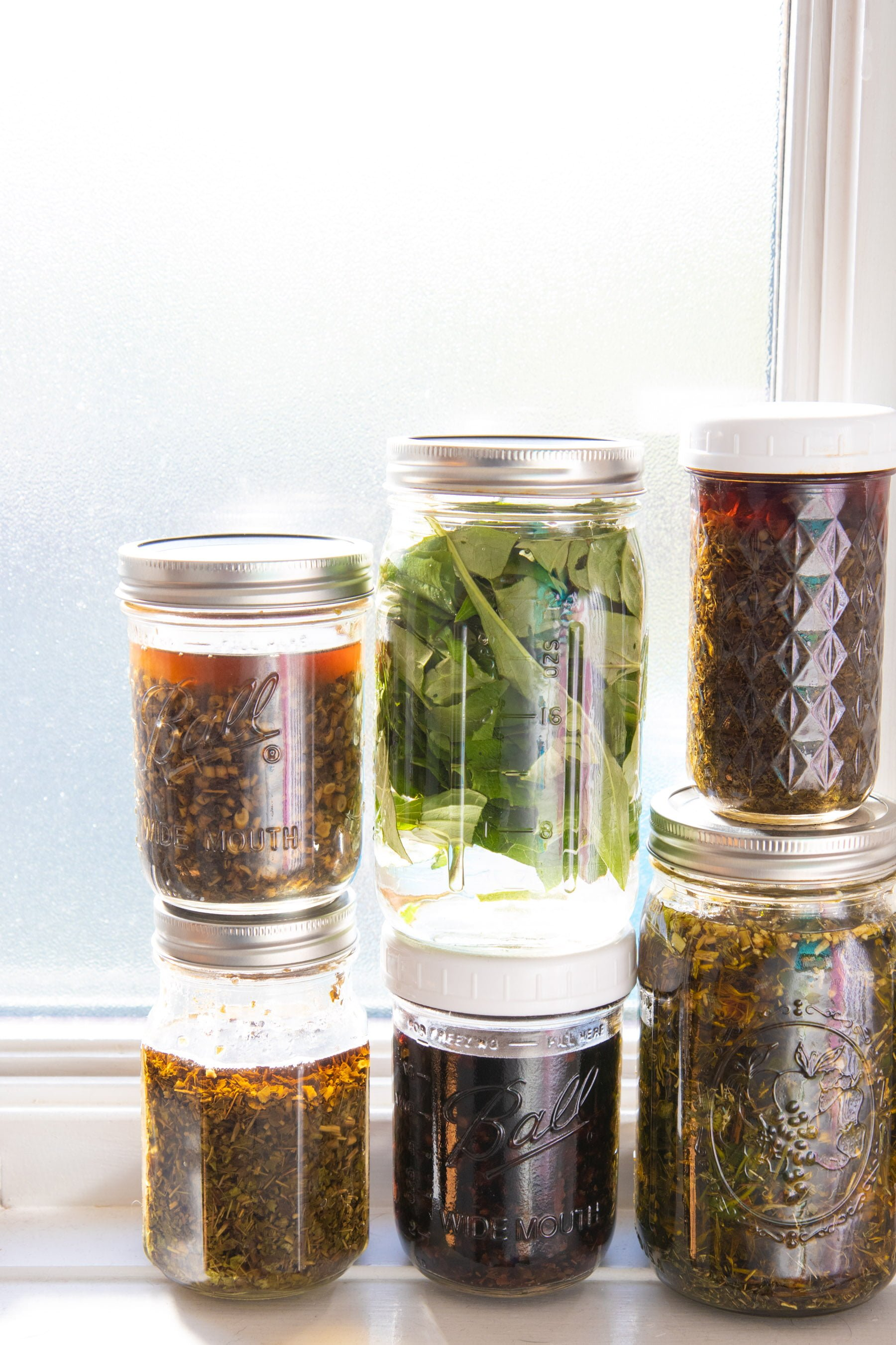 Glass mason jars holding tinctures of cold-busting herbal tea blends