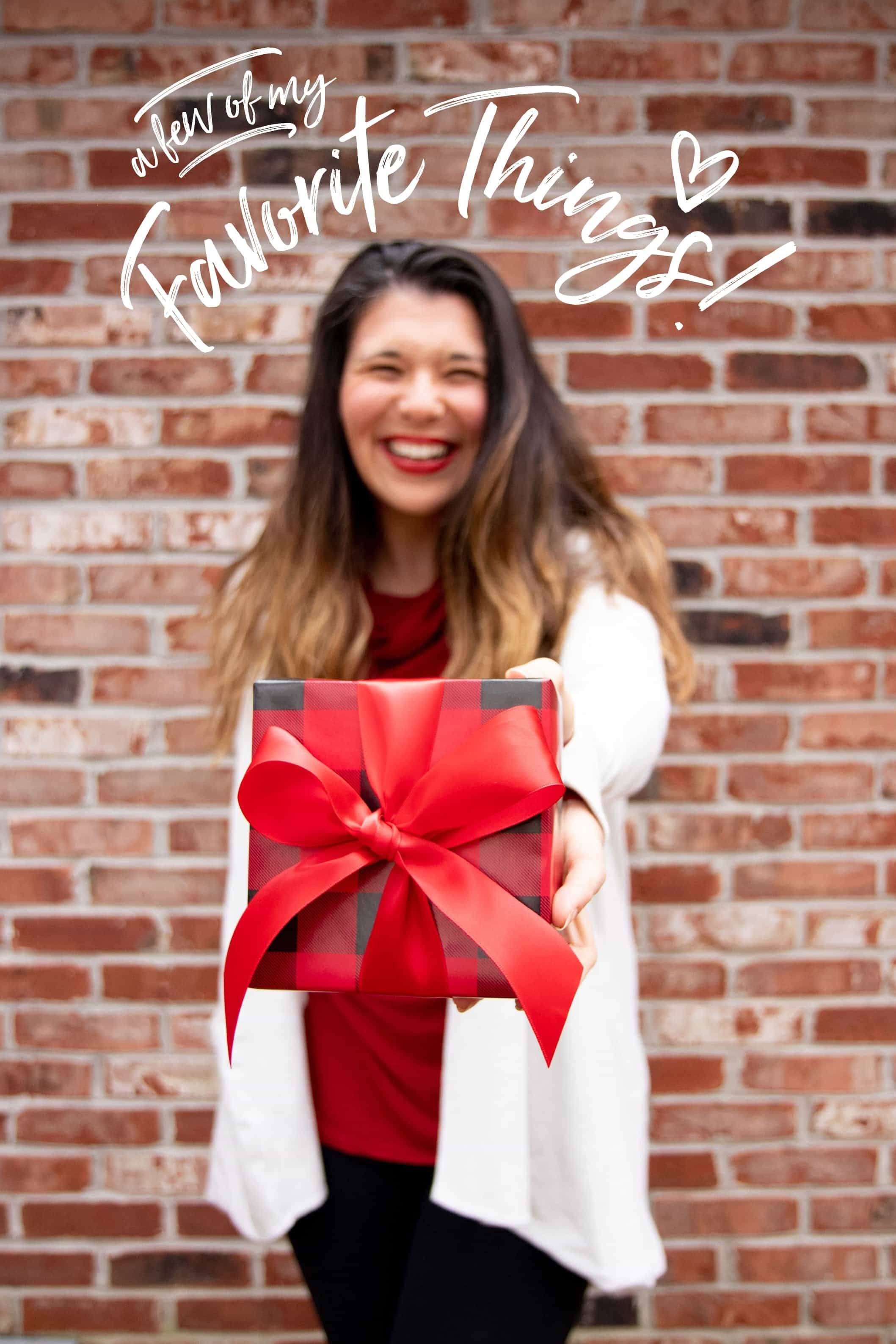 """Brunette woman holding out a wrapped gift, with the text """"a few of my Favorite Things"""" over her head"""