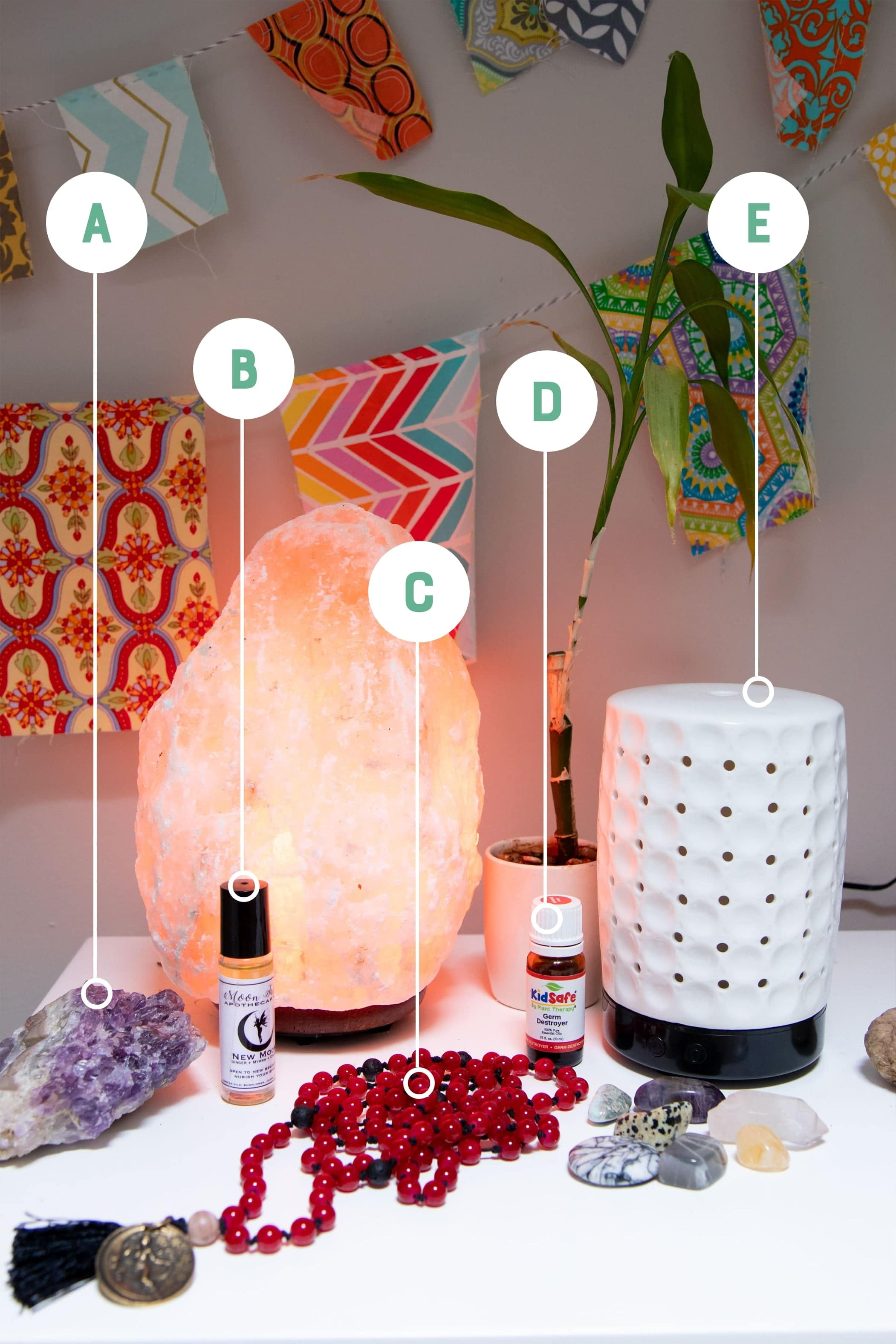 Natural home items arranged on a white table and labeled with letters: salt lamp, amethyst crystal, essential oils and diffuser, and a mala.