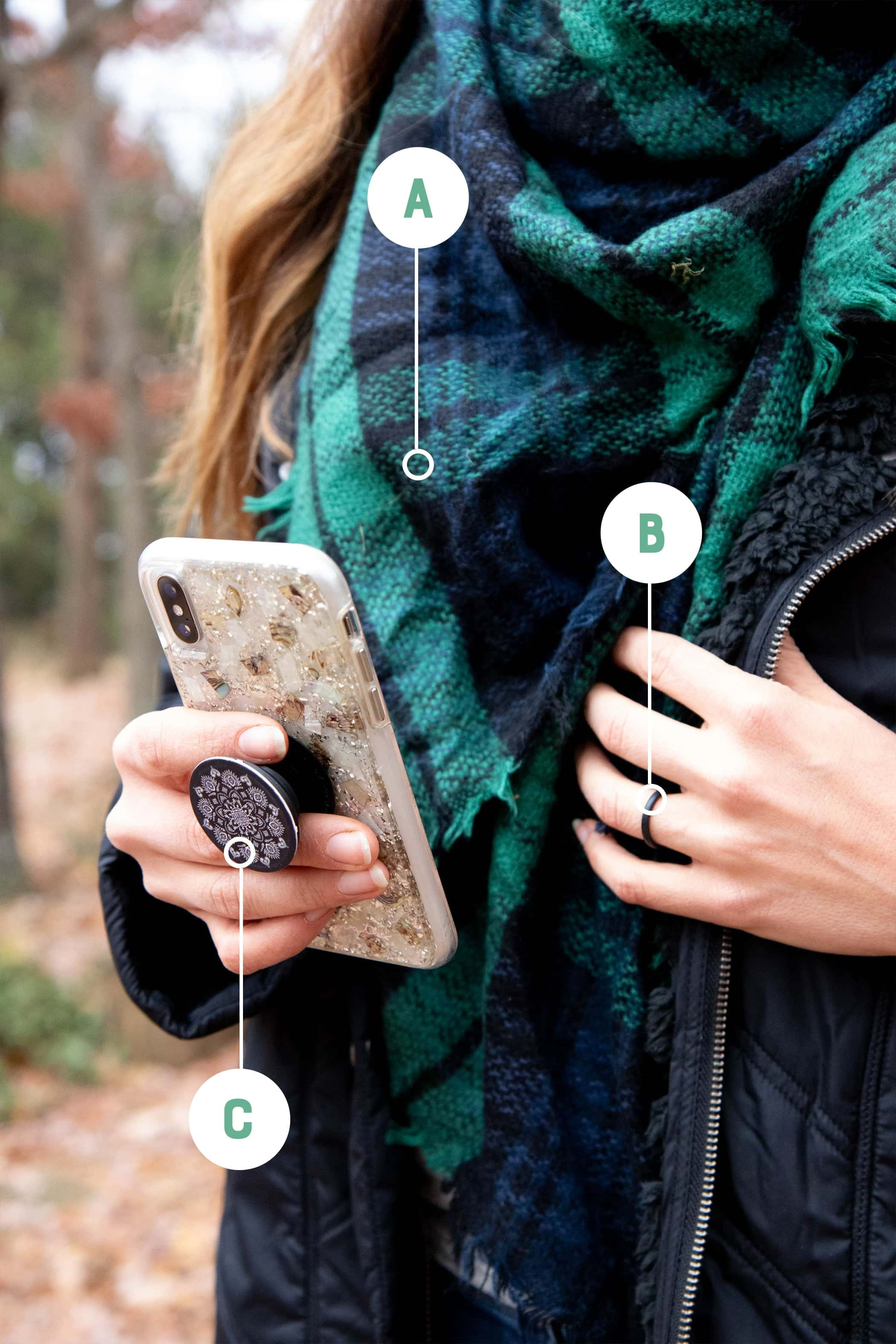 A woman's torso with a blanket scarf, silicone ring, and popsocket labeled with letters
