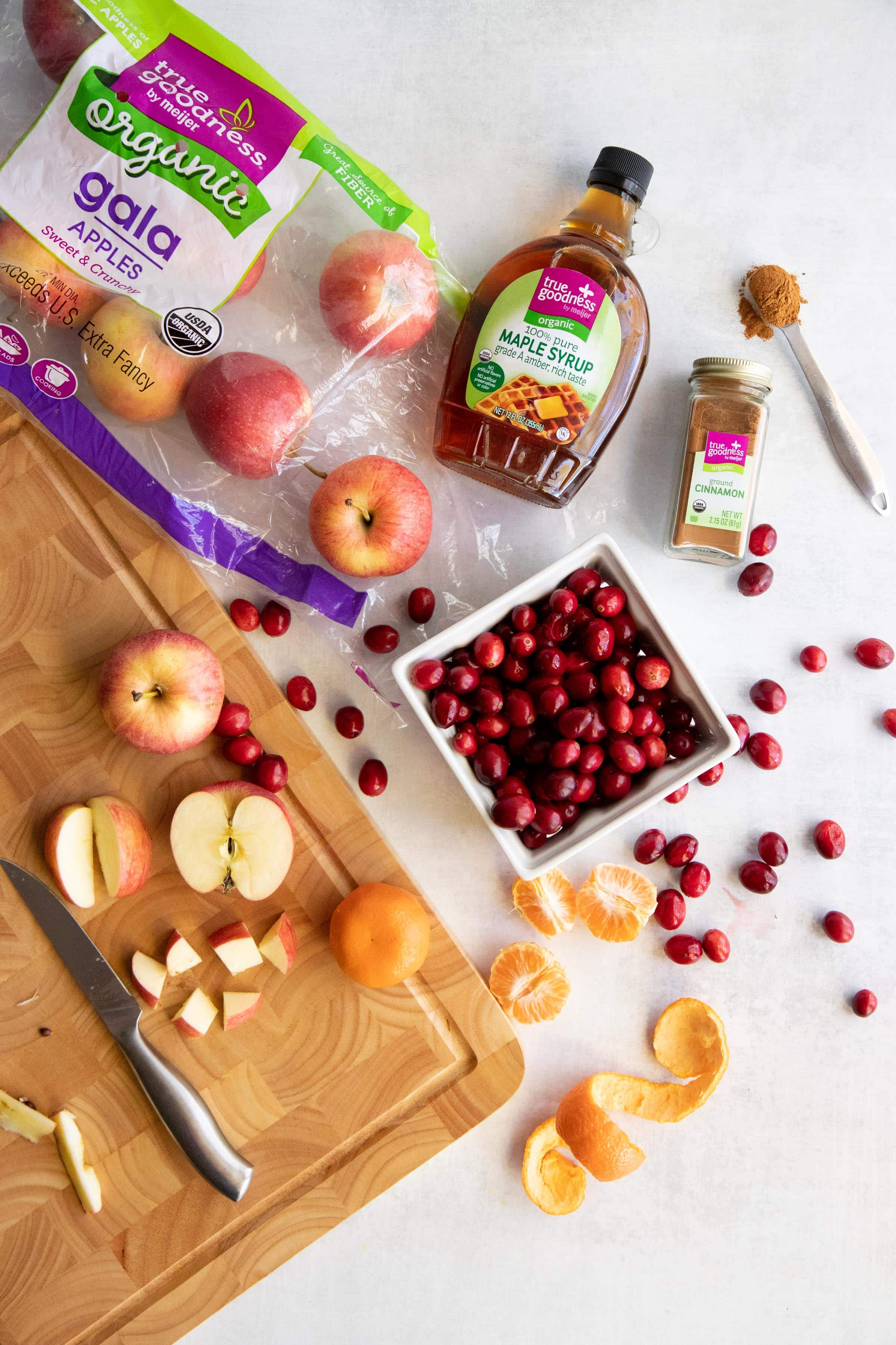 Ingredients for Chunky Cranberry Applesauce with a cutting board - cranberries, bag of Gala apples, maple syrup, spics, and citrus