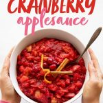 """Hands holding a white bowl of Chunky Cranberry Applesauce. Text overlay reads """"Chunky Cranberry Applesauce - Naturally Sweetened"""""""