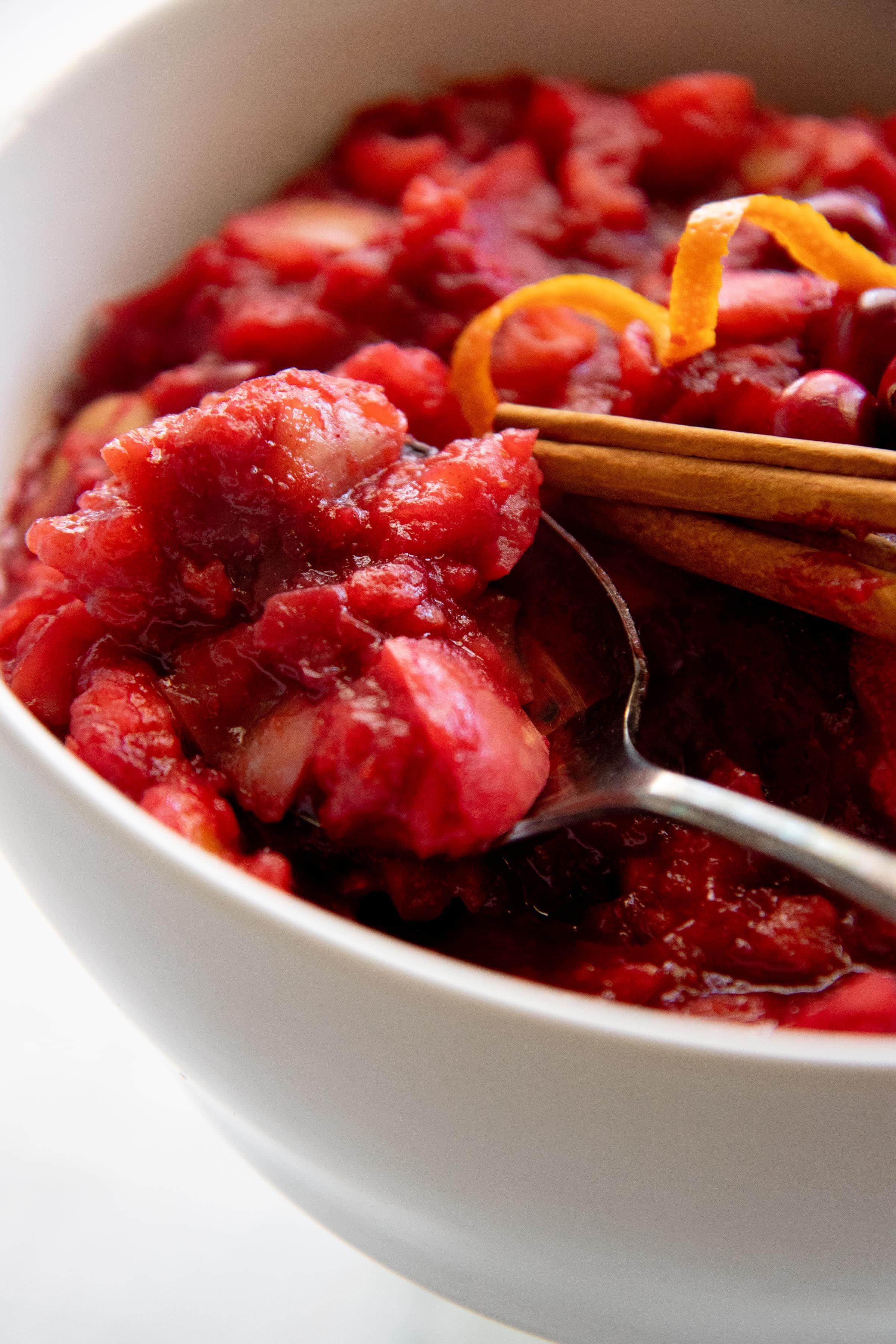Spoon dipping into a white bowl of Chunky Cranberry Applesauce