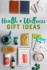 "Natural health items arranged on a gray backdrop: a ceramic neti pot, natural deodorant, face and hair masks, a dry brush, an ebook, bath salts, notebooks. A text overlay reads ""Health + Wellness Gift Ideas."""