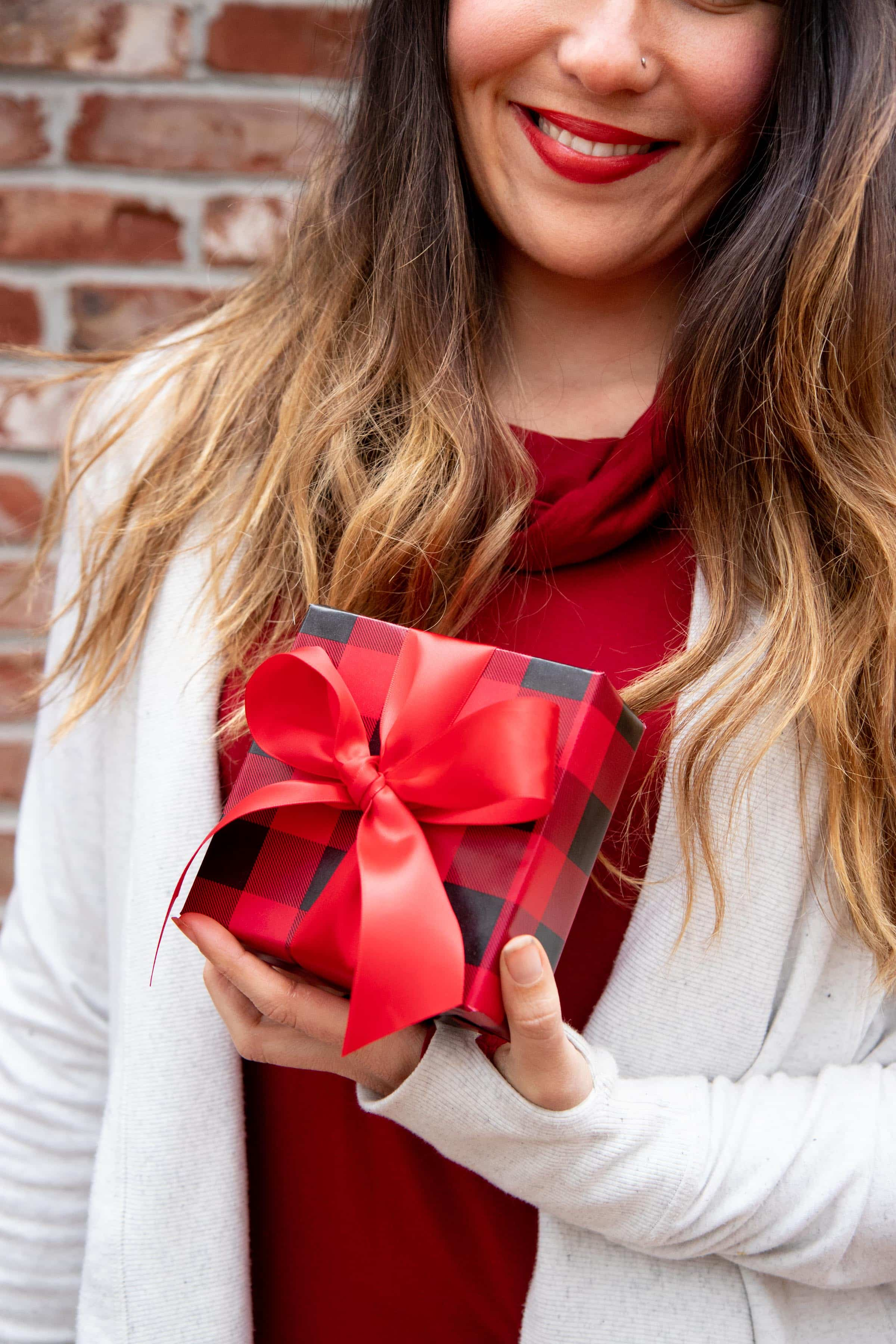 Close up of a smiling woman holding a red-wrapped gift