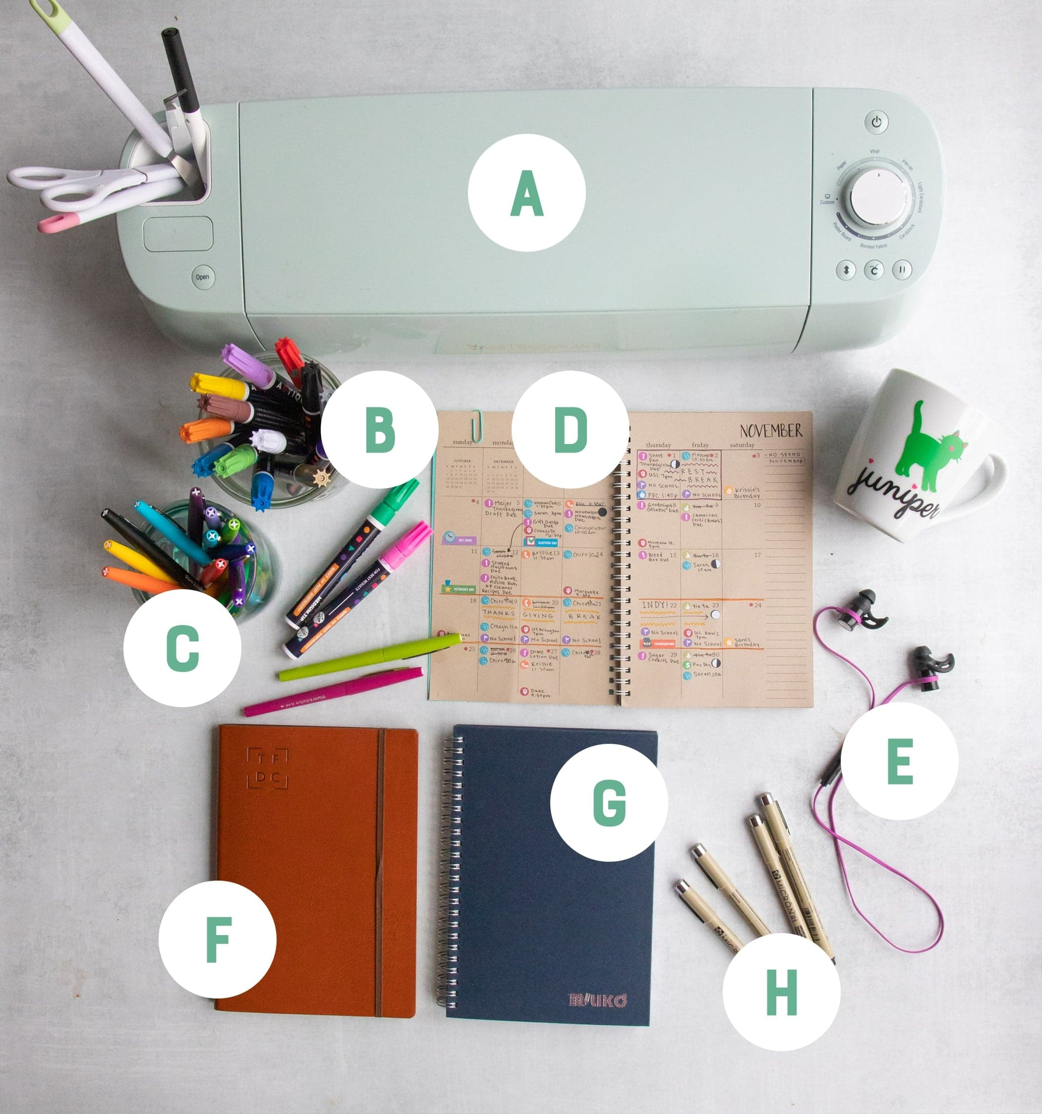 Office items arranged on a gray backdrop and labeled with letters: notebooks, a Cricut, pens in jars, headphones, and an open planner