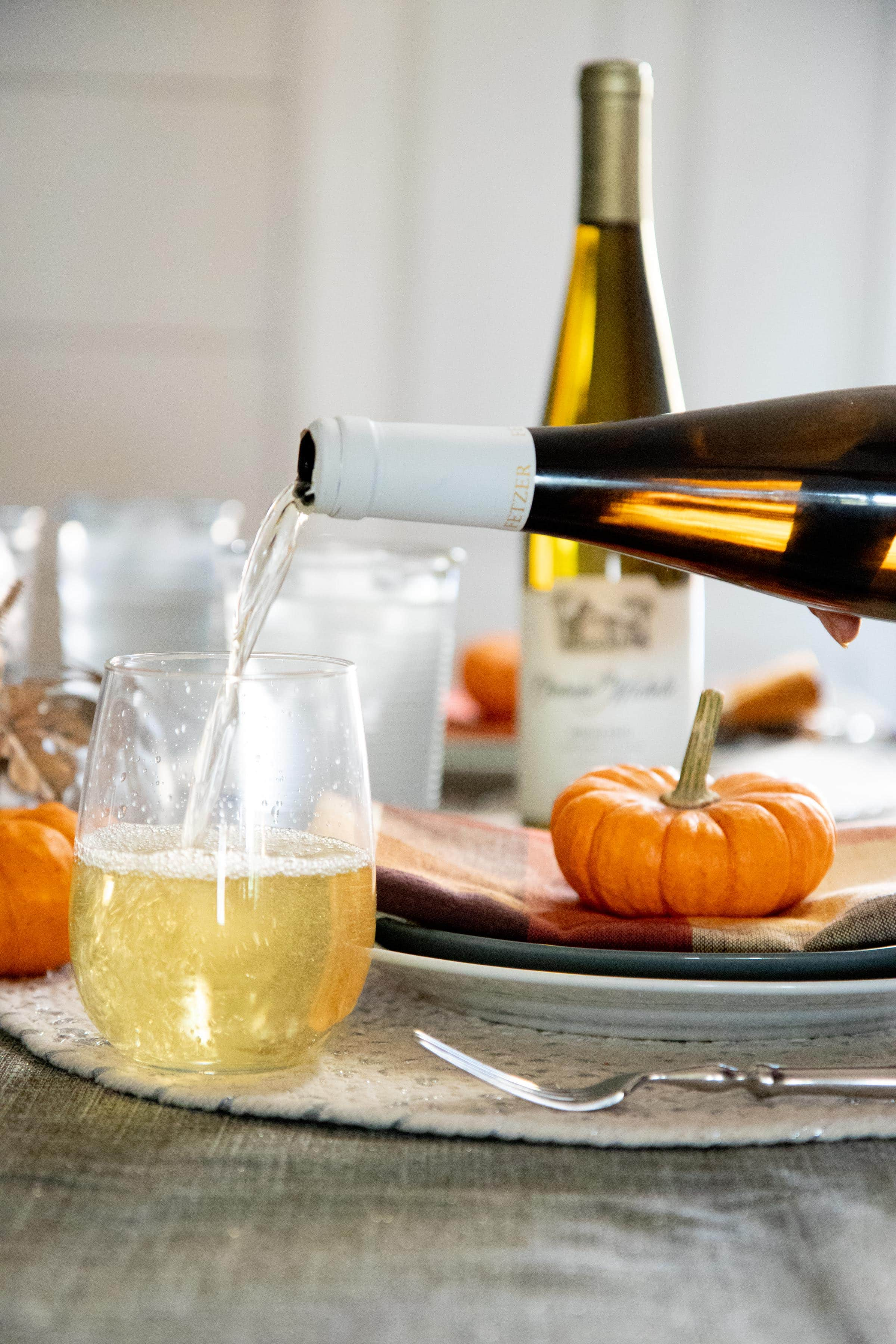 White wine being poured into a stemless glass on a table with fall decorations