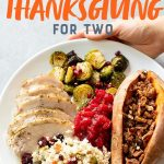 """Hands holding a plate of Thanksgiving food - turkey, Brussels sprouts, cranberry sauce, sweet potatoes, and cauliflower rice pilaf. Text overlay reads """"Sheet Pan Paleo Thanksgiving Dinner for Two."""""""