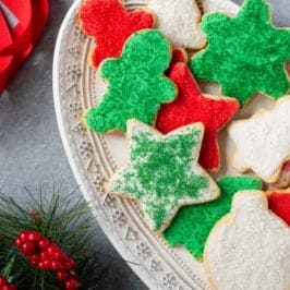 Grain-Free Paleo Sugar Cookies with Coconut Butter Frosting and Christmas sprinkles on a white platter