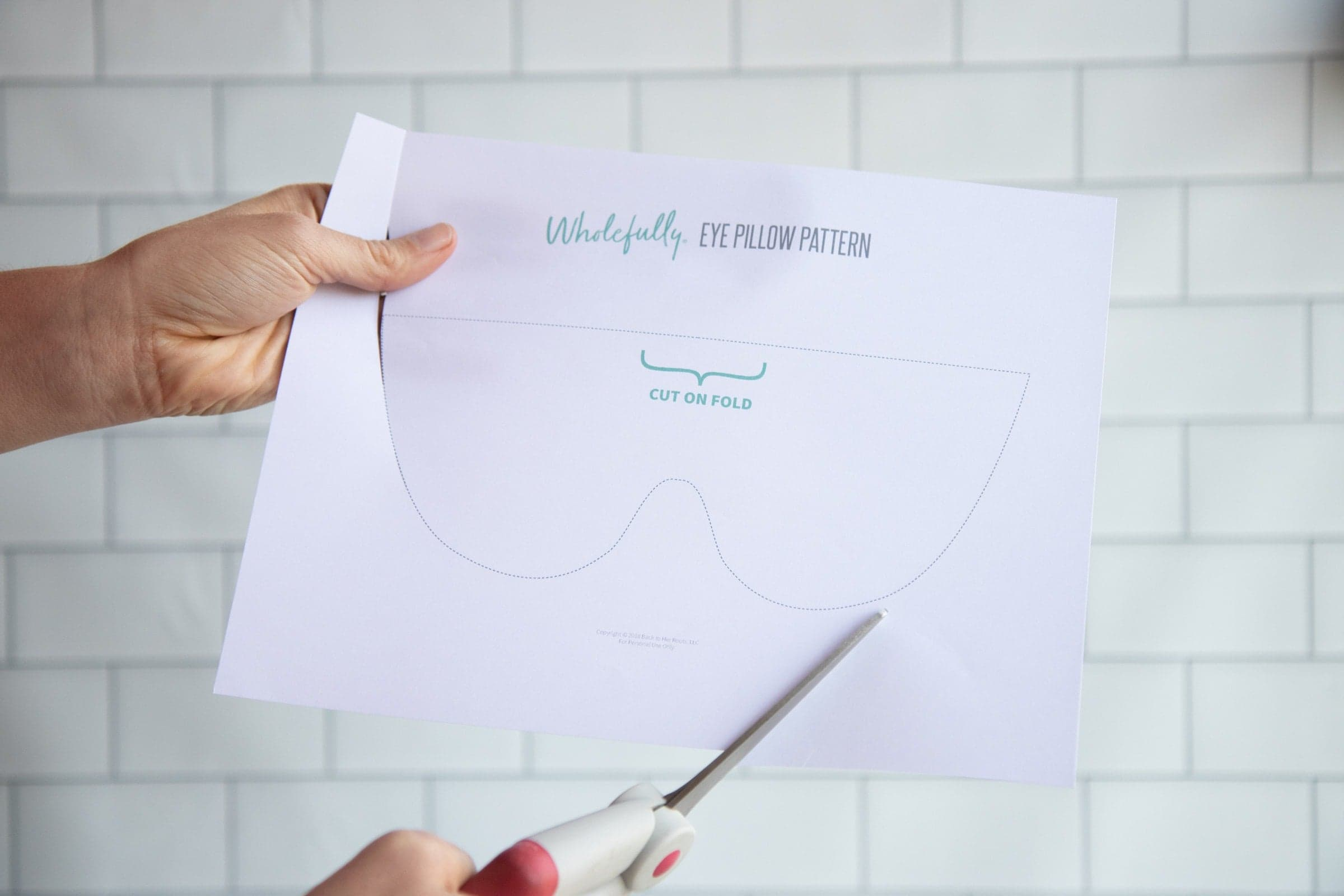 Scissors cutting out the paper pattern for Soothing Headache Eye Masks