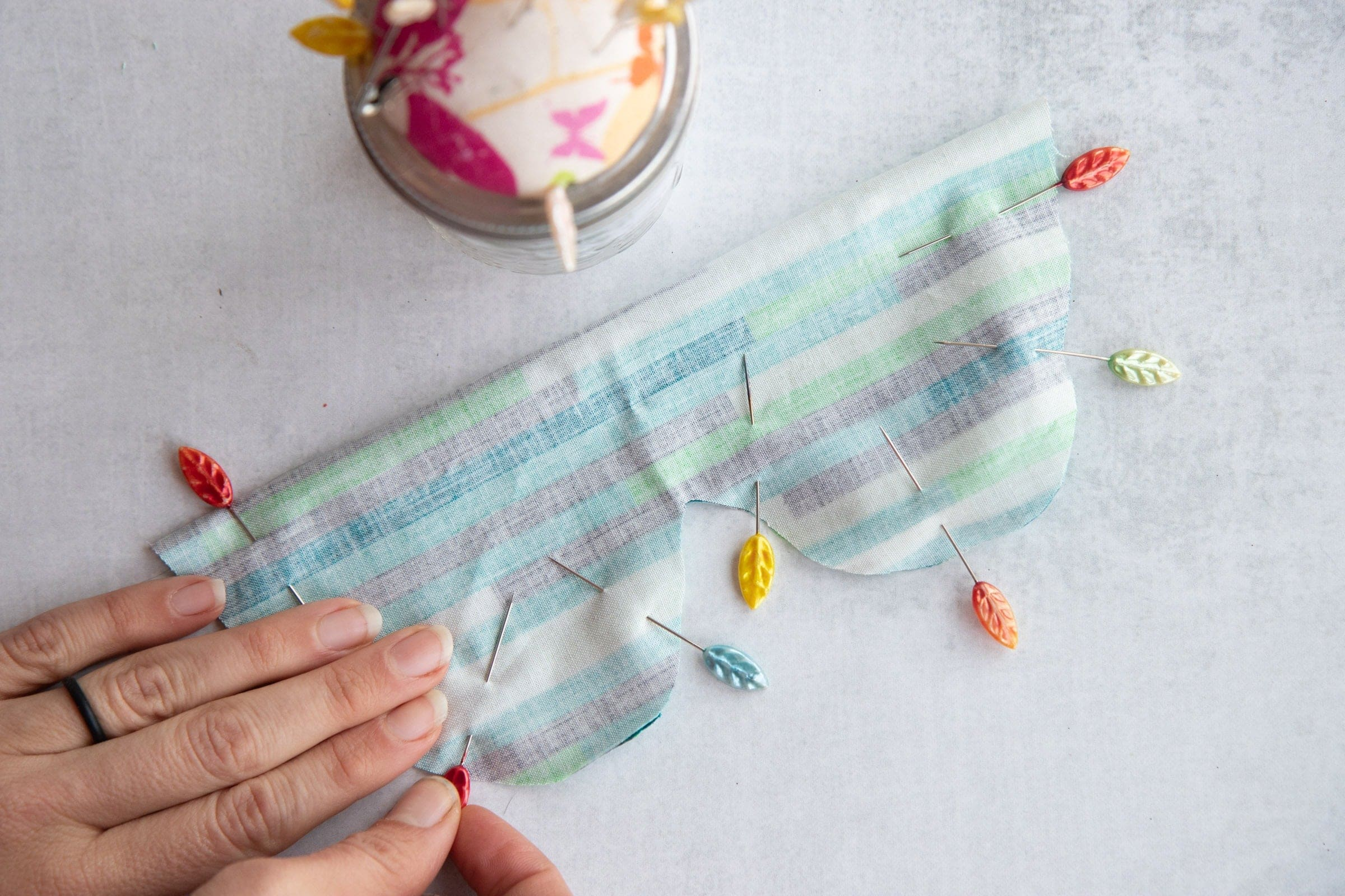 Pins surrounding the edge of fabric for a Soothing Headache Eye Mask