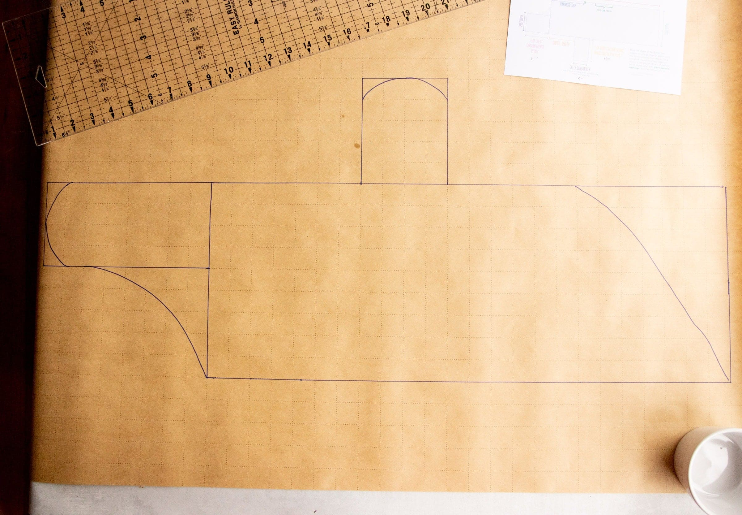 Pattern for a dog coat on pattern paper, with the edges of the pattern curved