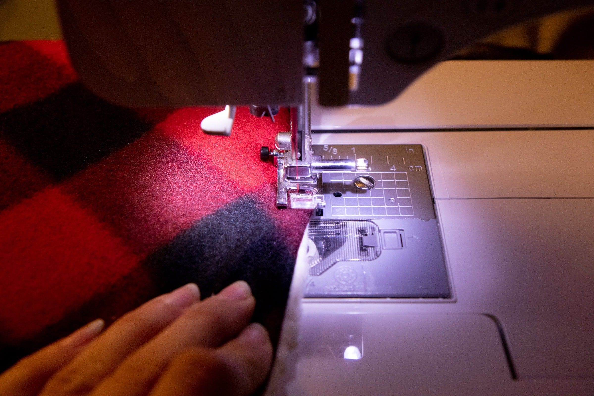 Plaid fabric being fed through a sewing machine