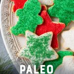 "Grain-Free Paleo Sugar Cookies with Coconut Butter Frosting and Christmas sprinkles on a white platter. A text overlay reads ""Paleo Sugar Cookies."""