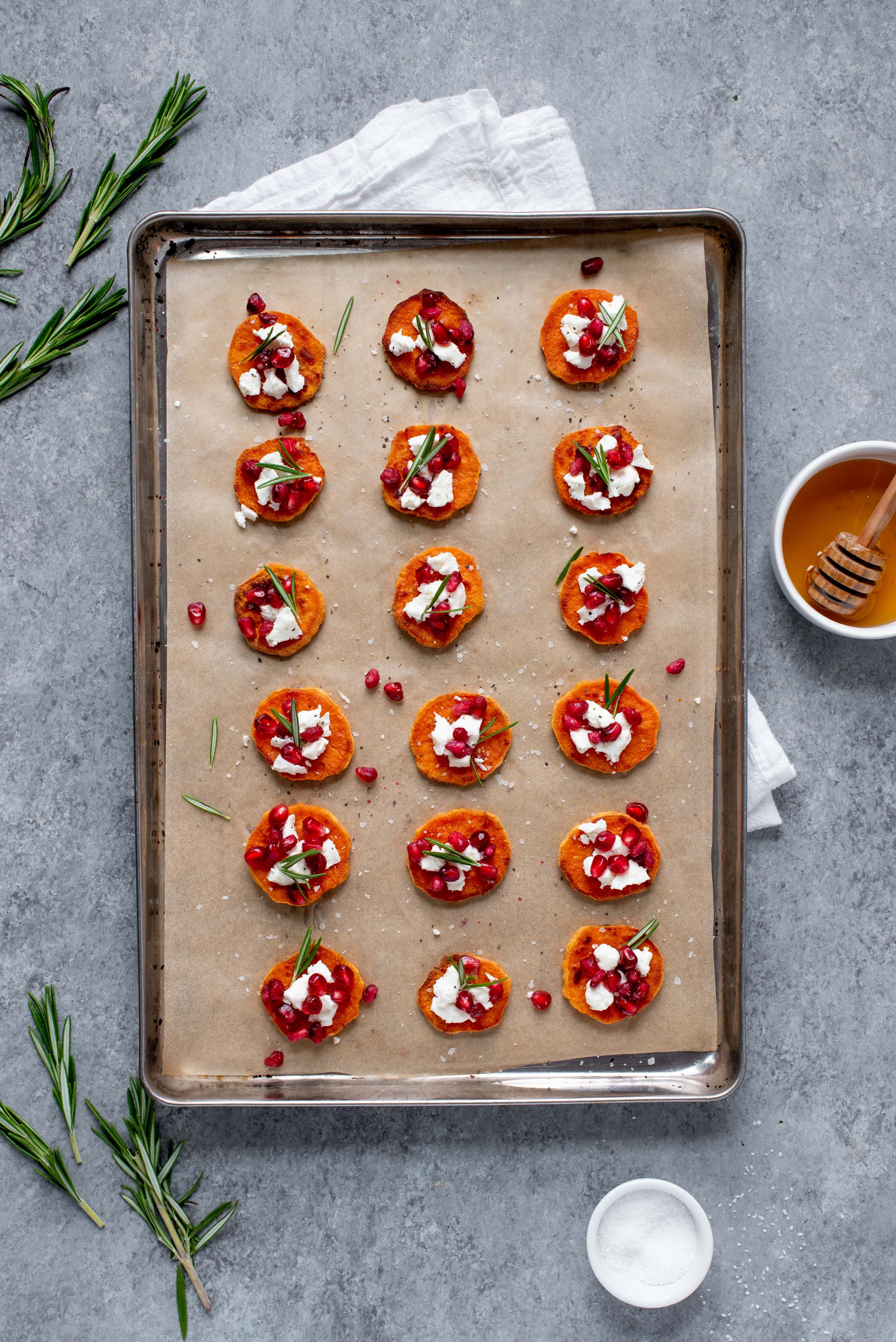 Sweet Potato Crostini with Goat Cheese and Pomegranate spread out on a baking sheet lined with parchment paper