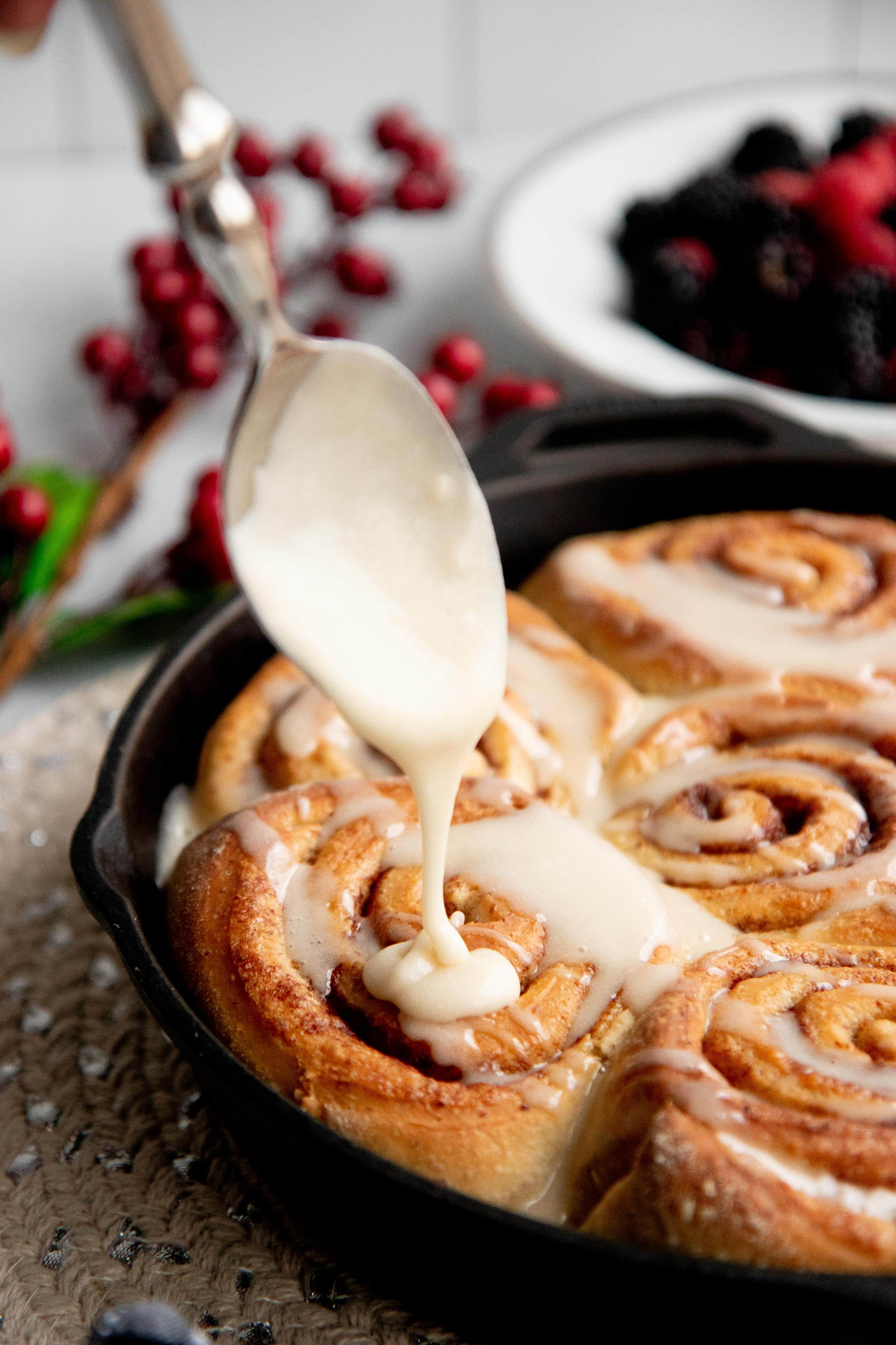 Spoon drizzling icing onto baked vegan cinnamon rolls in a cast iron skillet.