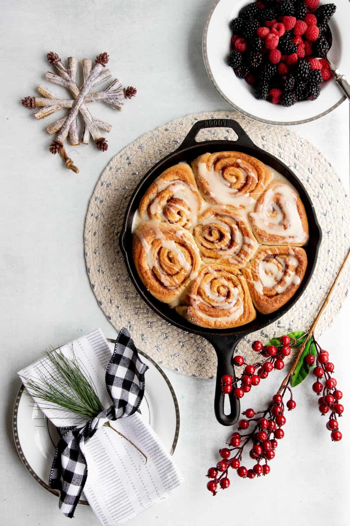 Overhead of a cast iron skillet filled with make-ahead vegan cinnamon rolls drizzled with icing.