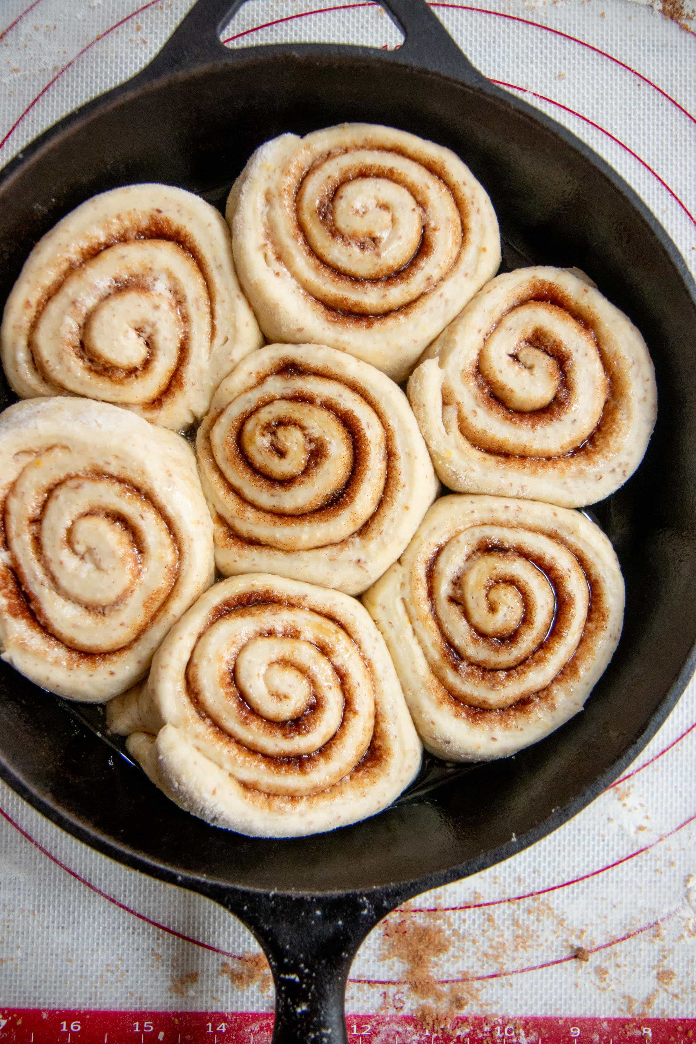 Unbaked Make-Ahead Vegan Cinnamon Rolls nestled in a cast iron skillet, ready to be baked
