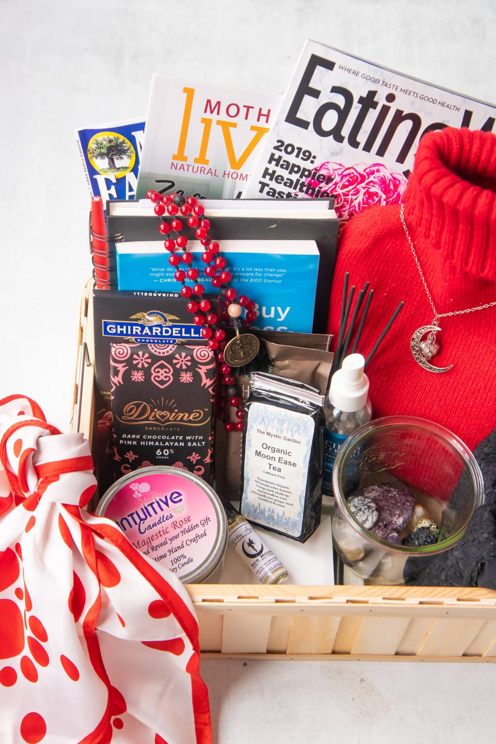 A bleed box, filled with all sorts of goodies - a red and white scarf, a candle, crystals, hot water bottle, magazines, books, a mala, and chocolate.