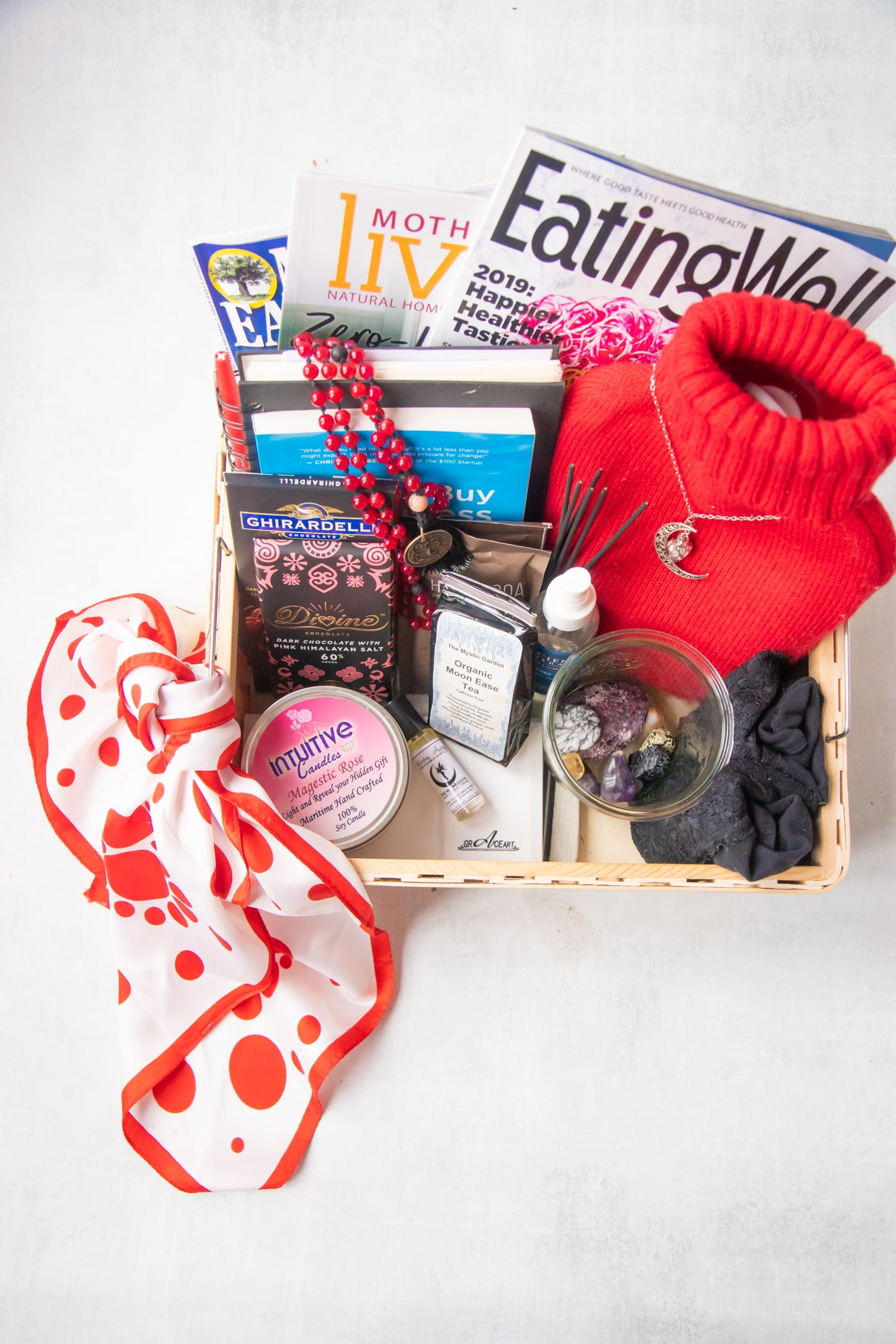 A bleed box, filled with all sorts of goodies - a red and white scarf, a candle, crystals, hot water bottle, magazines, books, and chocolate.