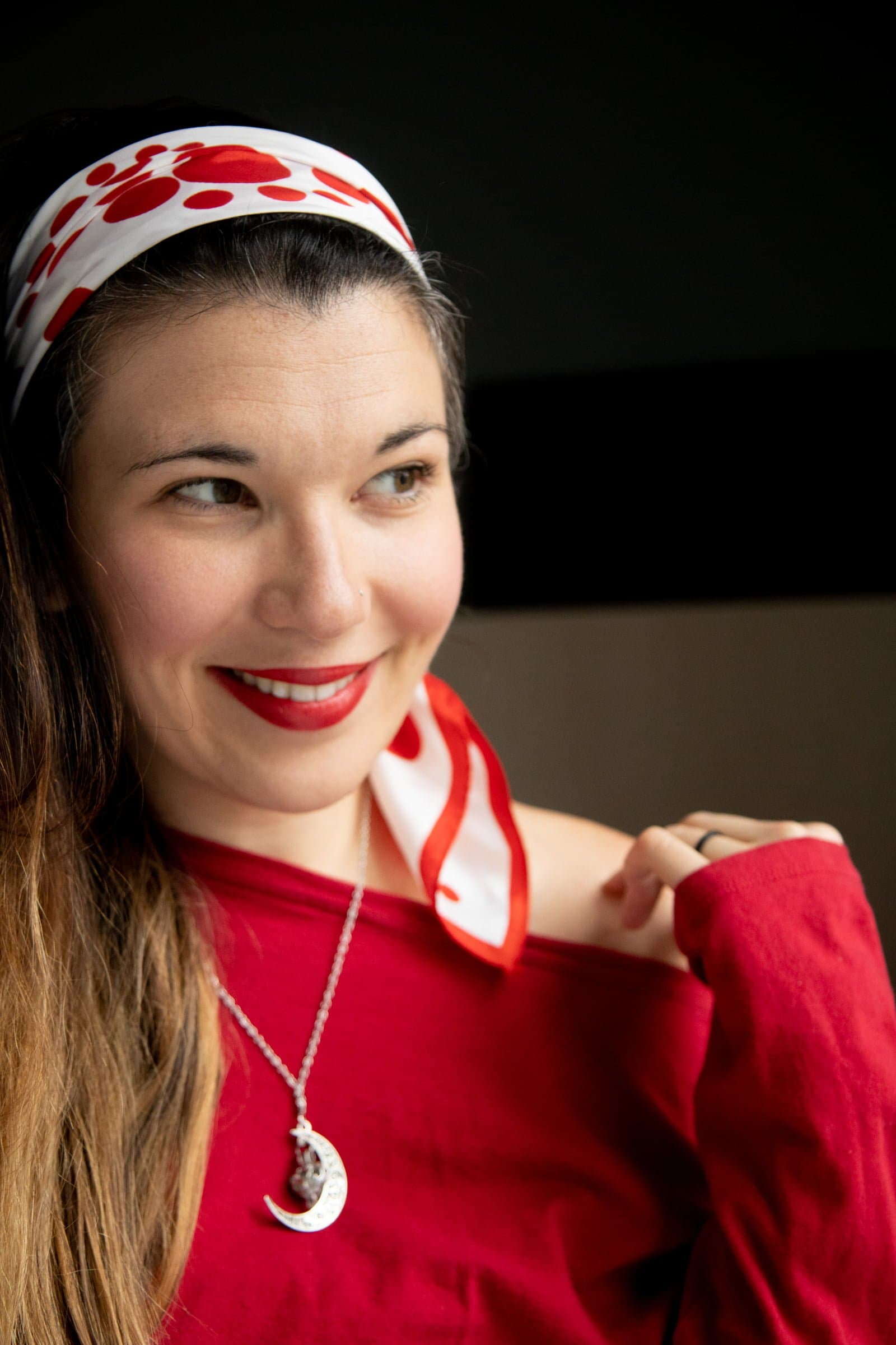 Brunette woman in a red sweater and moonstone necklace, with a red and white scarf wrapped around her hair