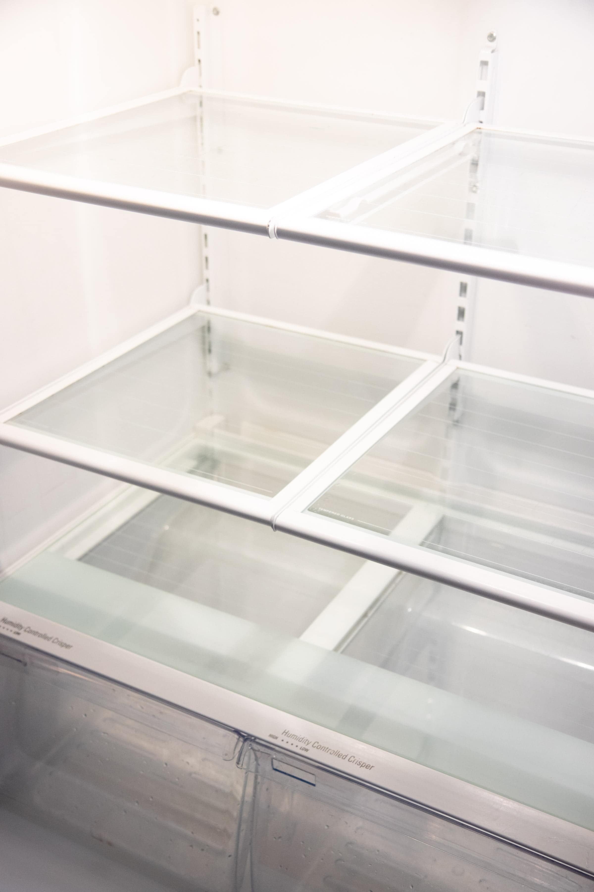 Empty refrigerator shelves that have been cleaned