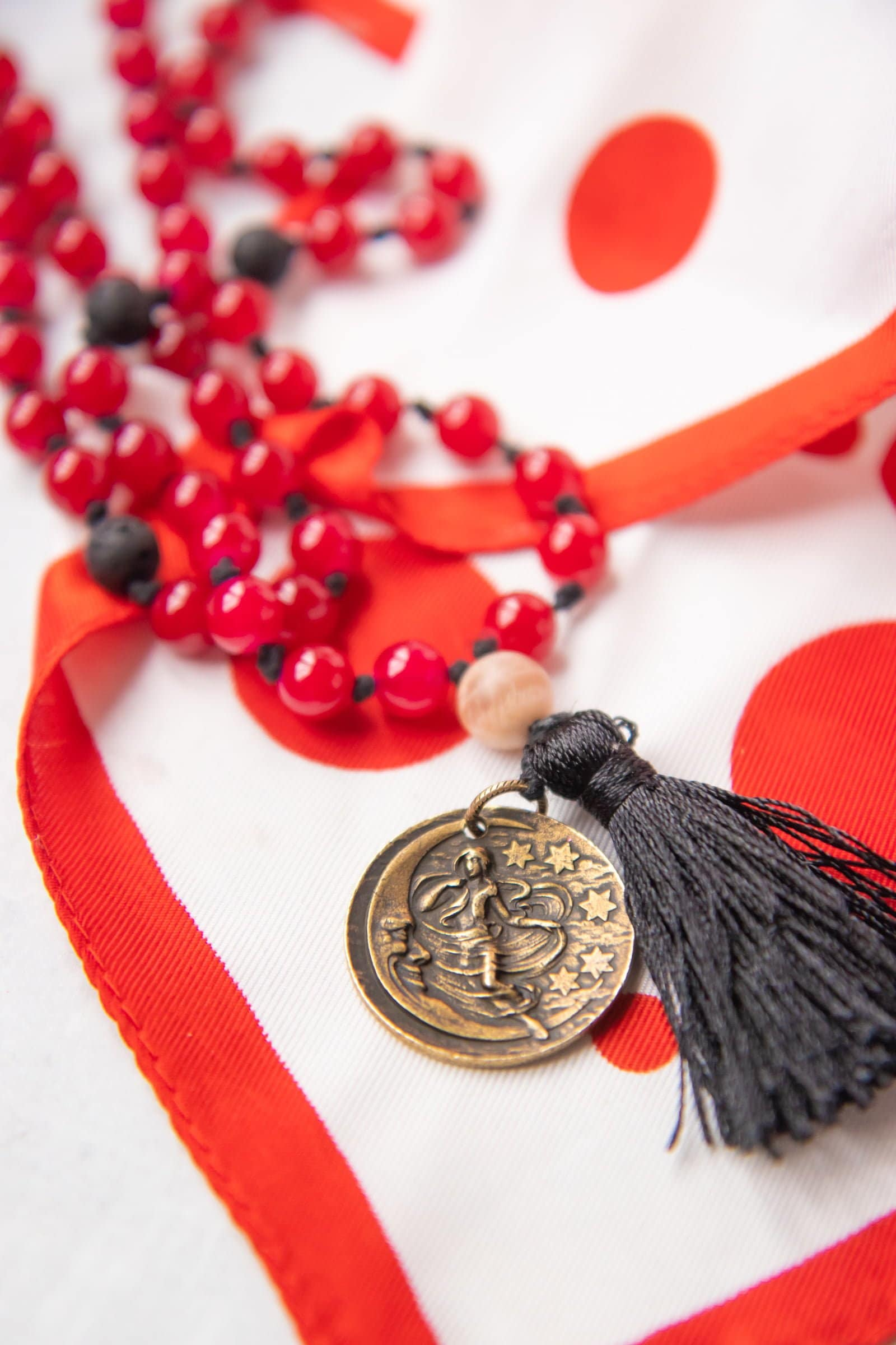 Close up of a red beaded mala with a moonstone, on top of a red and white scarf.