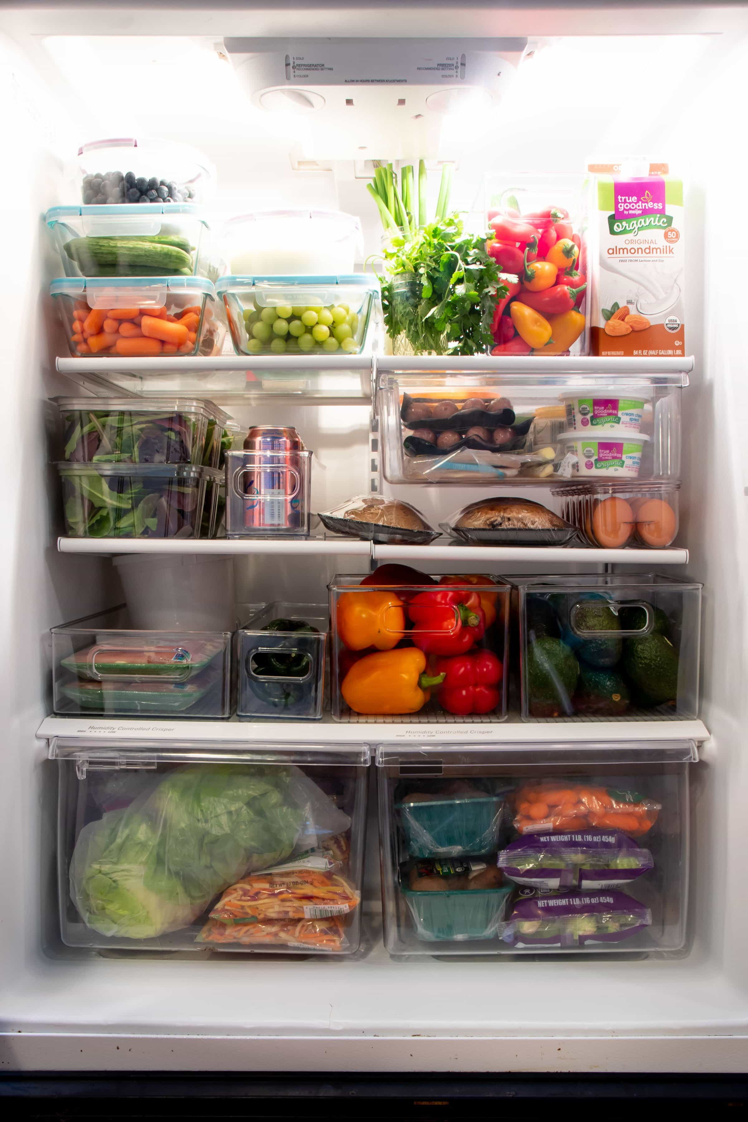 A clean, organized fridge filled mostly with produce