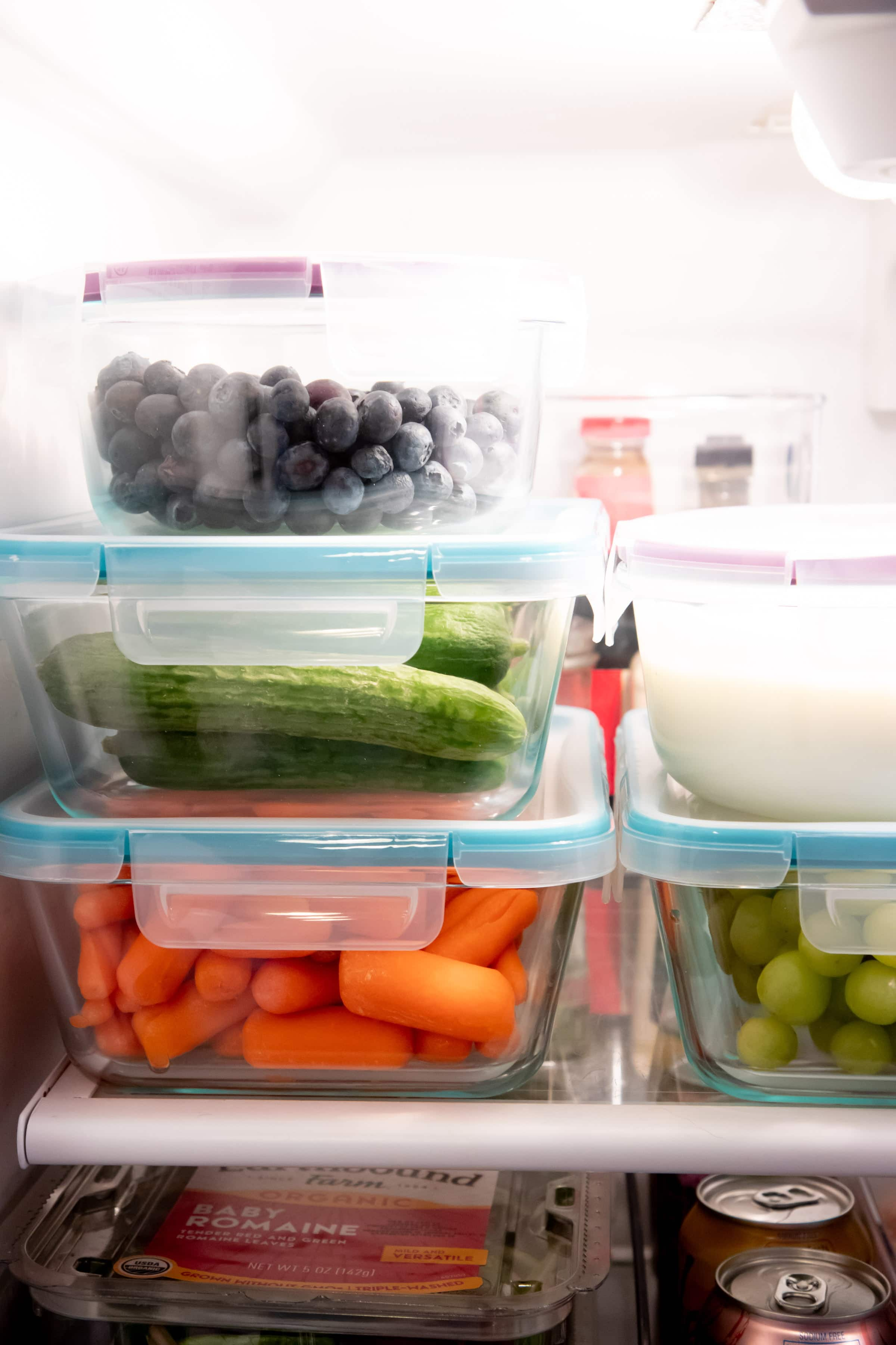 Close up of produce organized into glass containers in a refrigerator