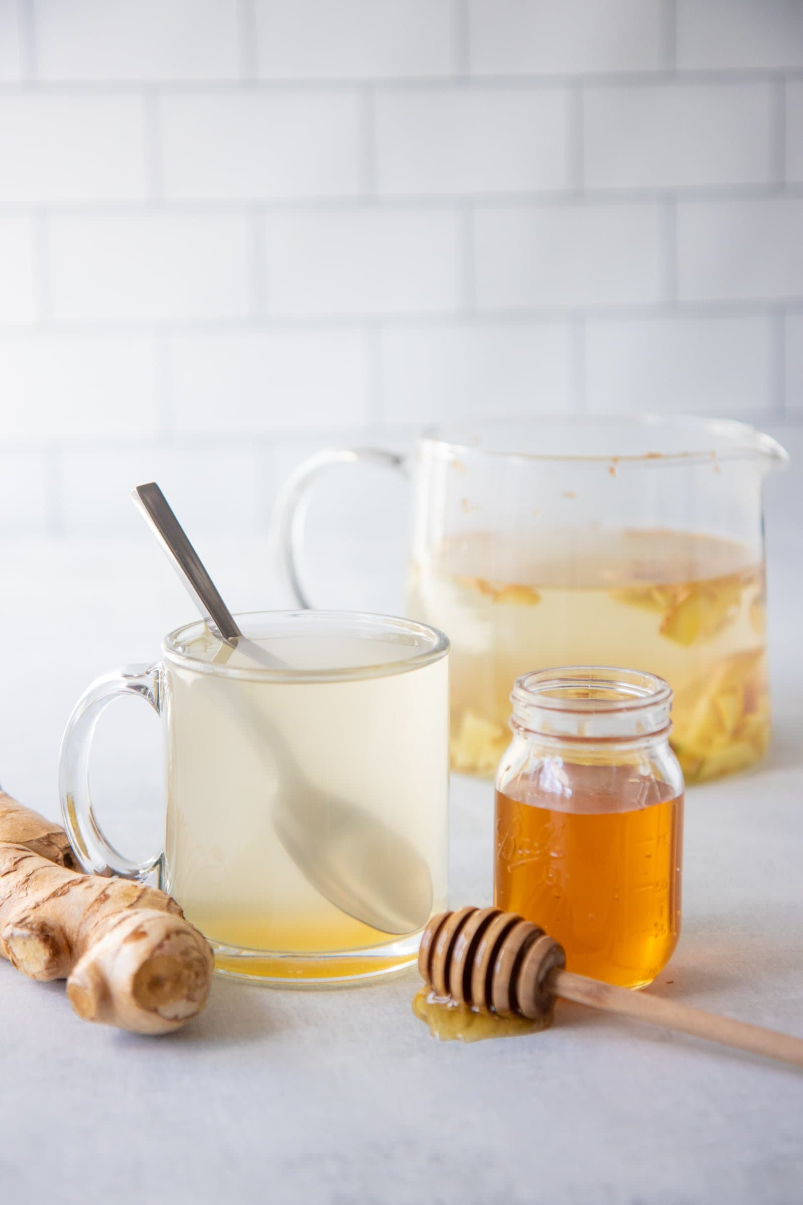 Clear glass of ginger tea and a jar of honey in the forefront, with a teapot of ginger tea in the background