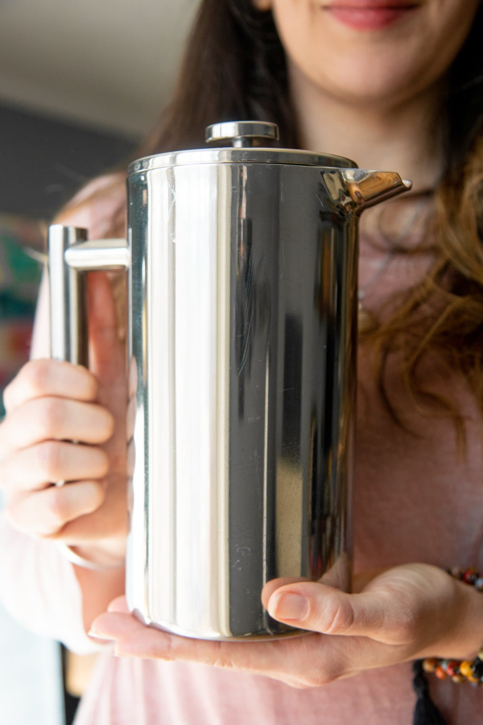 Long-haired woman holding up a stainless steel French press