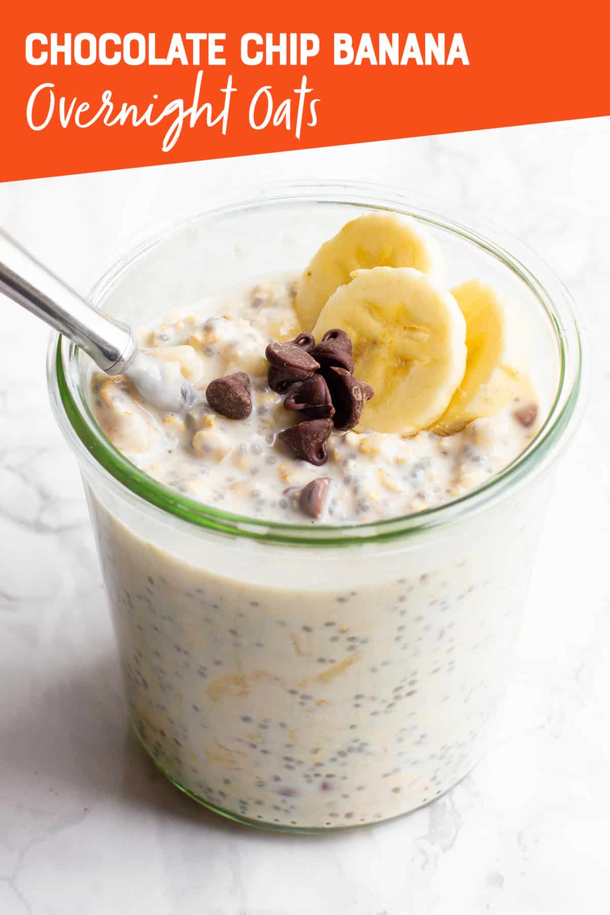 """A clear glass jar filled with Banana Chocolate Chip Overnight Oats, with a spoon sticking out. A text overlay reads """"Chocolate Chip Banana Overnight Oats."""""""