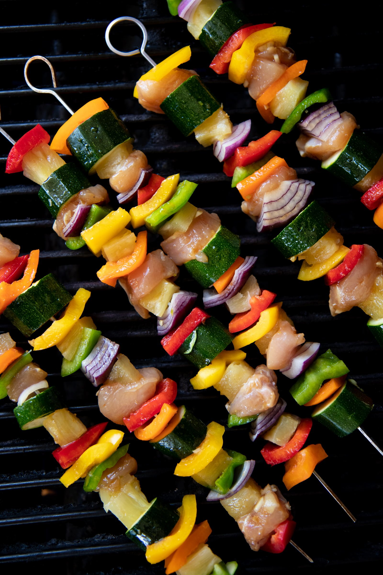 Metal skewers threaded with chicken, vegetables, and pineapple on top of a grill.