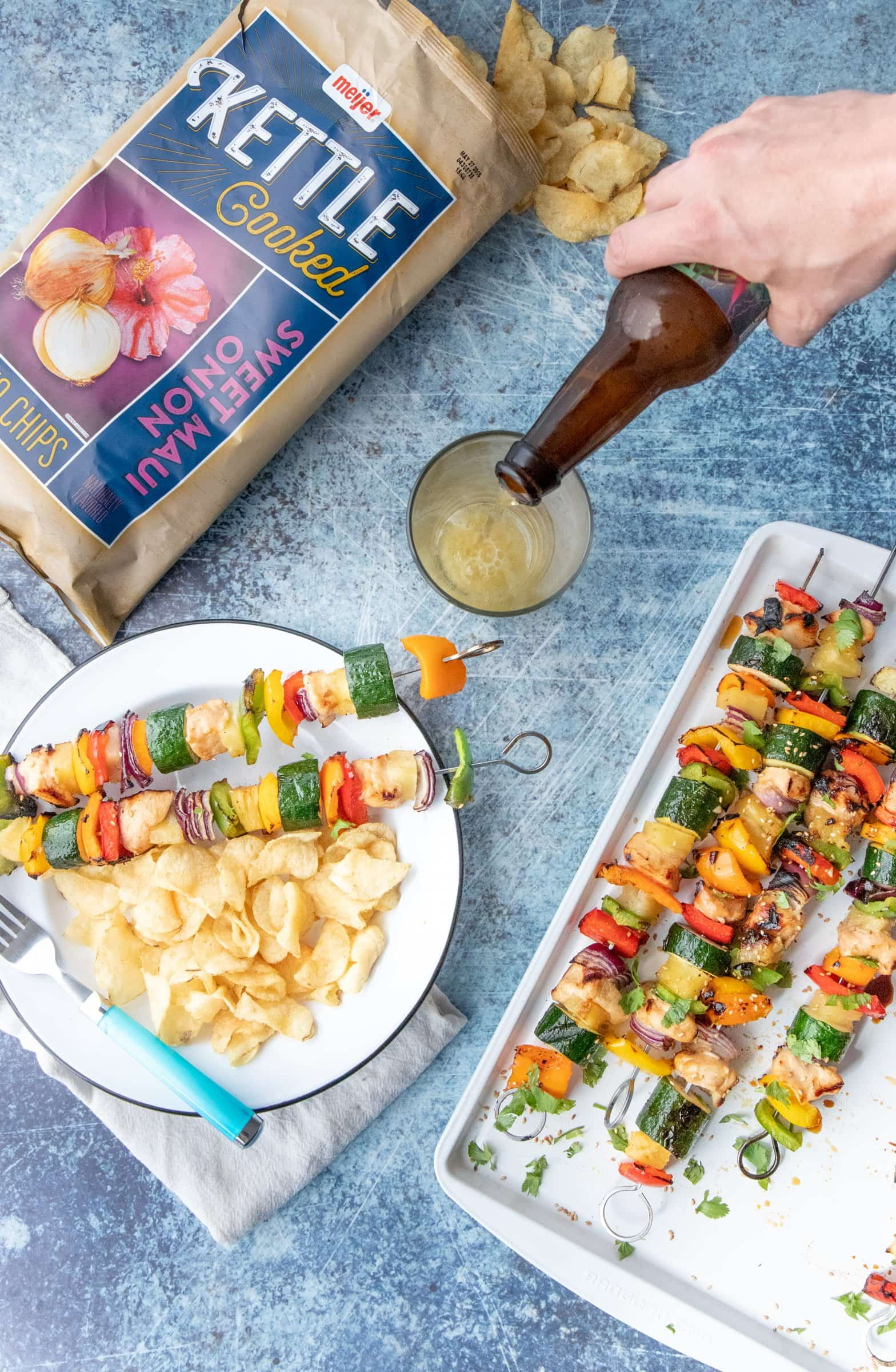 Hand pouring beer into a glass on a table full of Grilled Hawaiian Chicken Kabobs and kettle chips