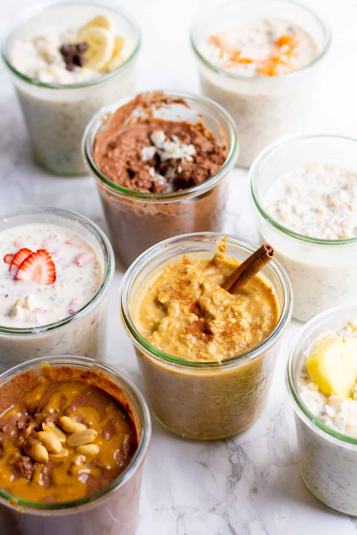 Eight different flavors of overnight oats, each in its own glass jar.